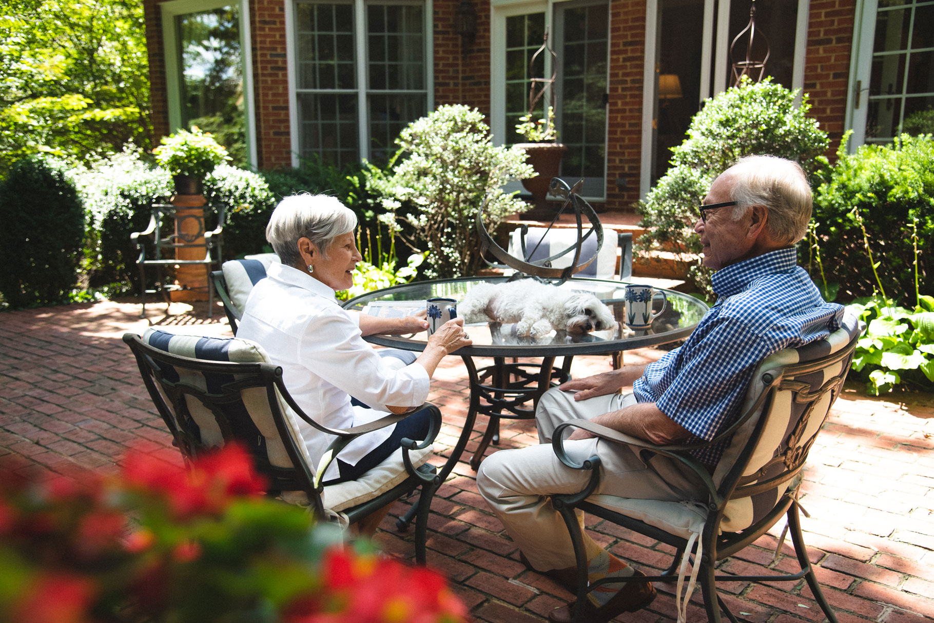 Gayle and her husband chat over coffee outside while their dog rests on a table.
