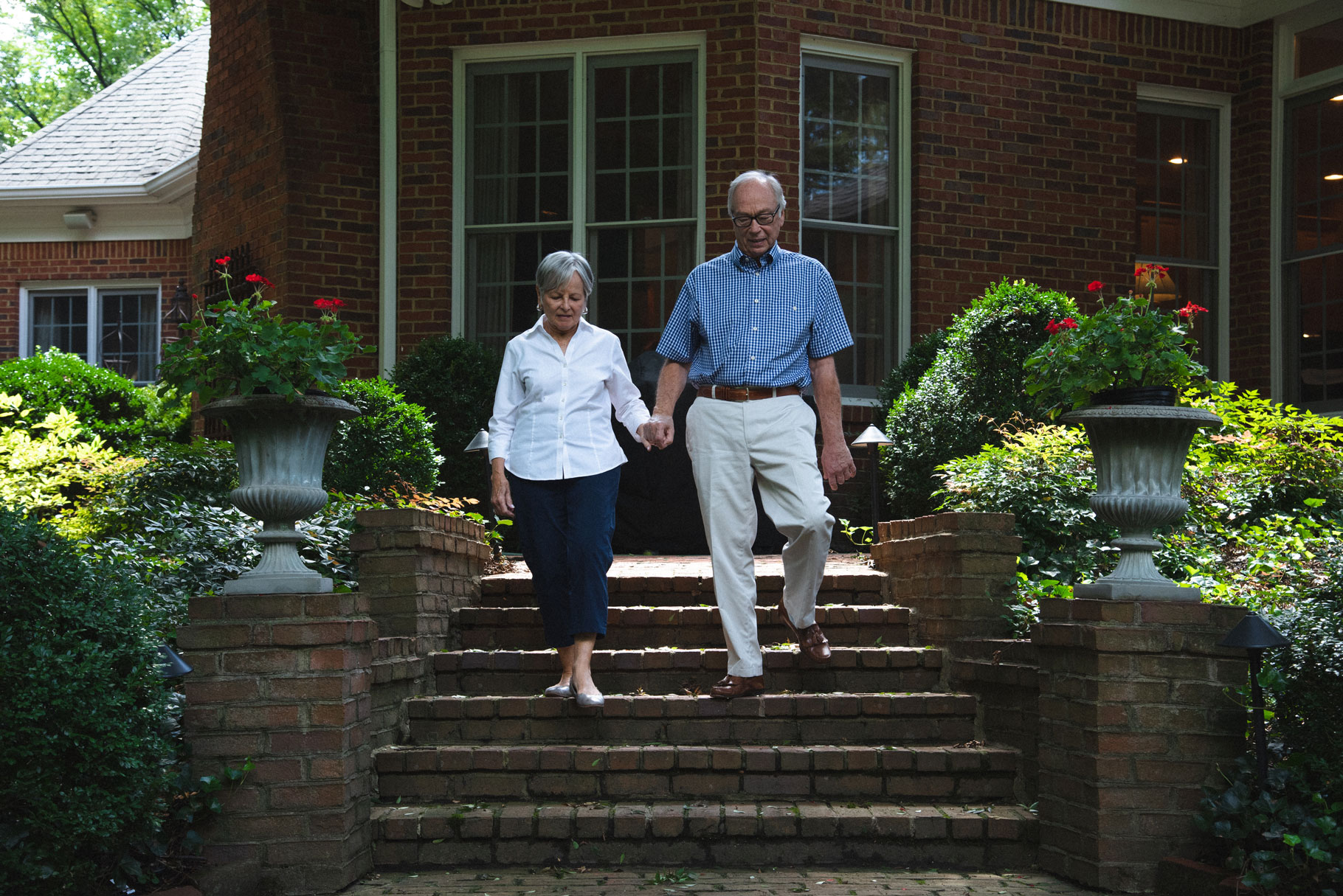 Gayle and her husband hold hands and walk down their front steps.