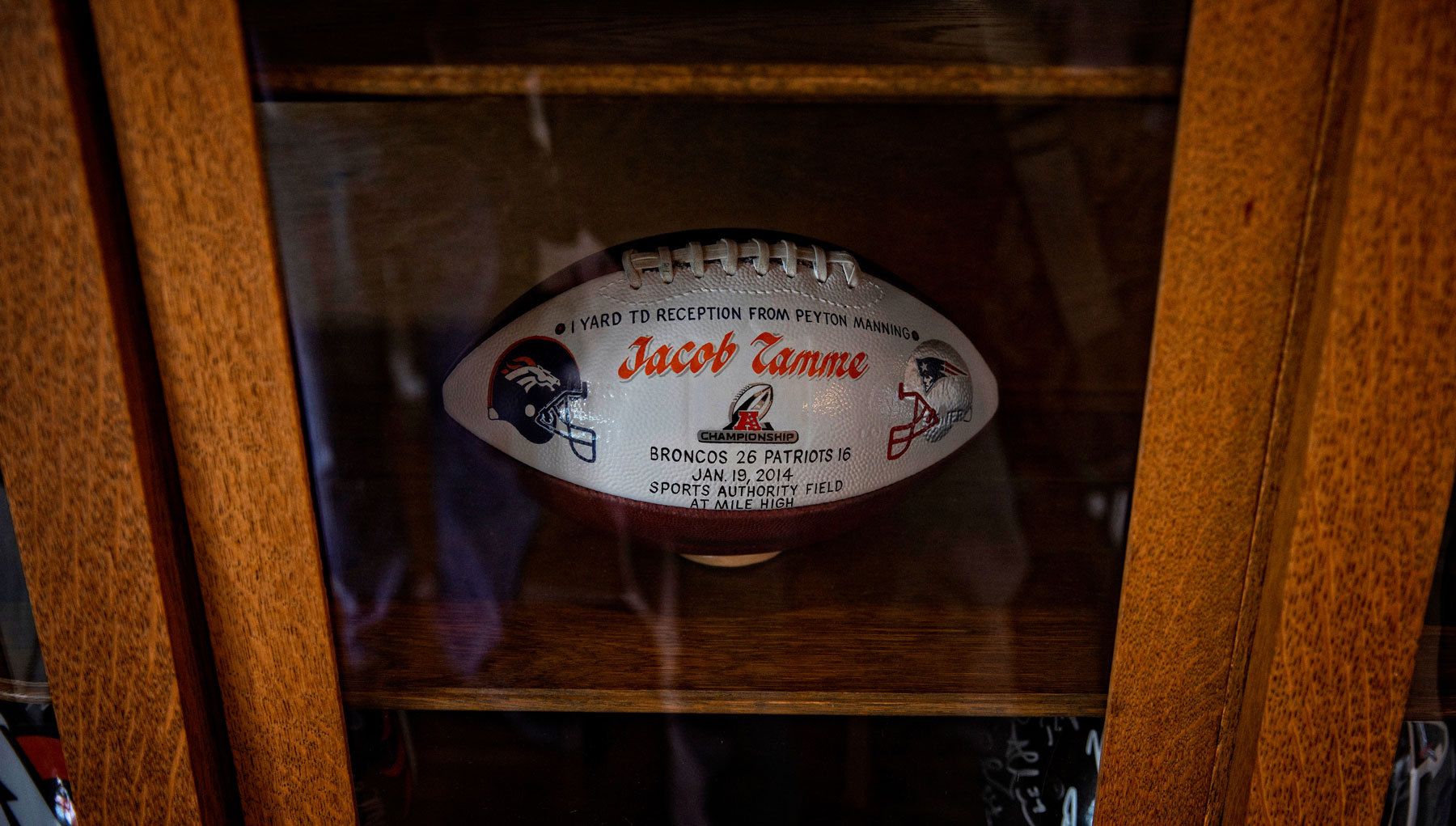 "A special football is displayed in a case that says ""1 yard TD reception from Peyton Manning. Jacob Tamme. Broncos 26 Patriots 15 Jan. 19 2014. Sports Authority Field at Mile High"""