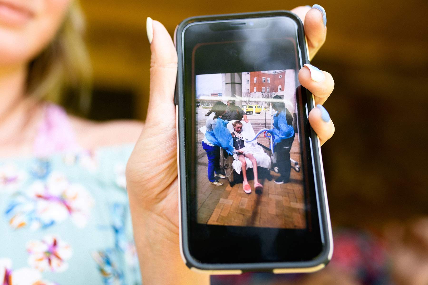 Breanna shows a photo on her phone of when she was being wheeled into the hospital for a lung transplant.