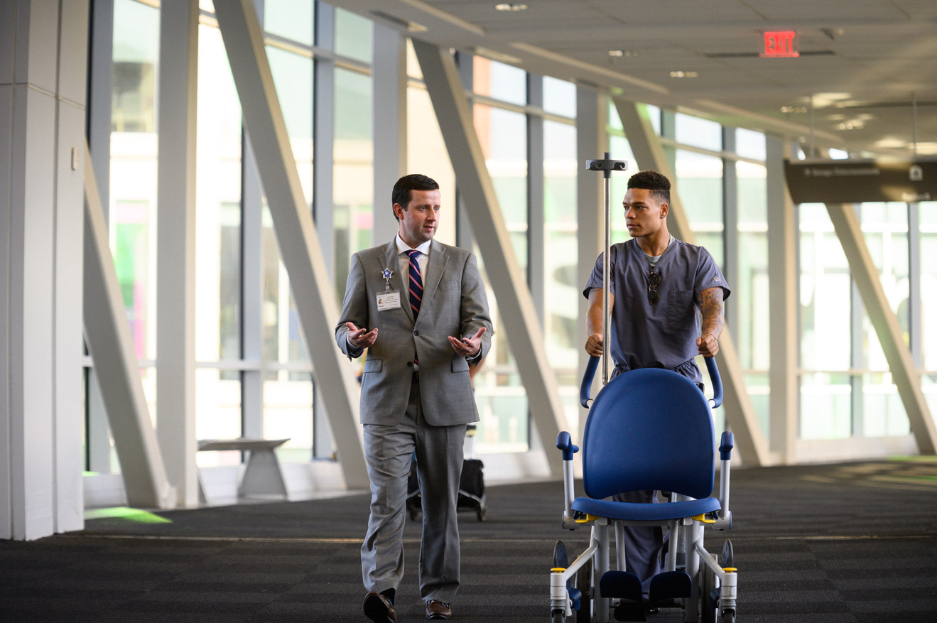 JJ chats with a football player working a shift pushing a chair down the hall at UK HealthCare.