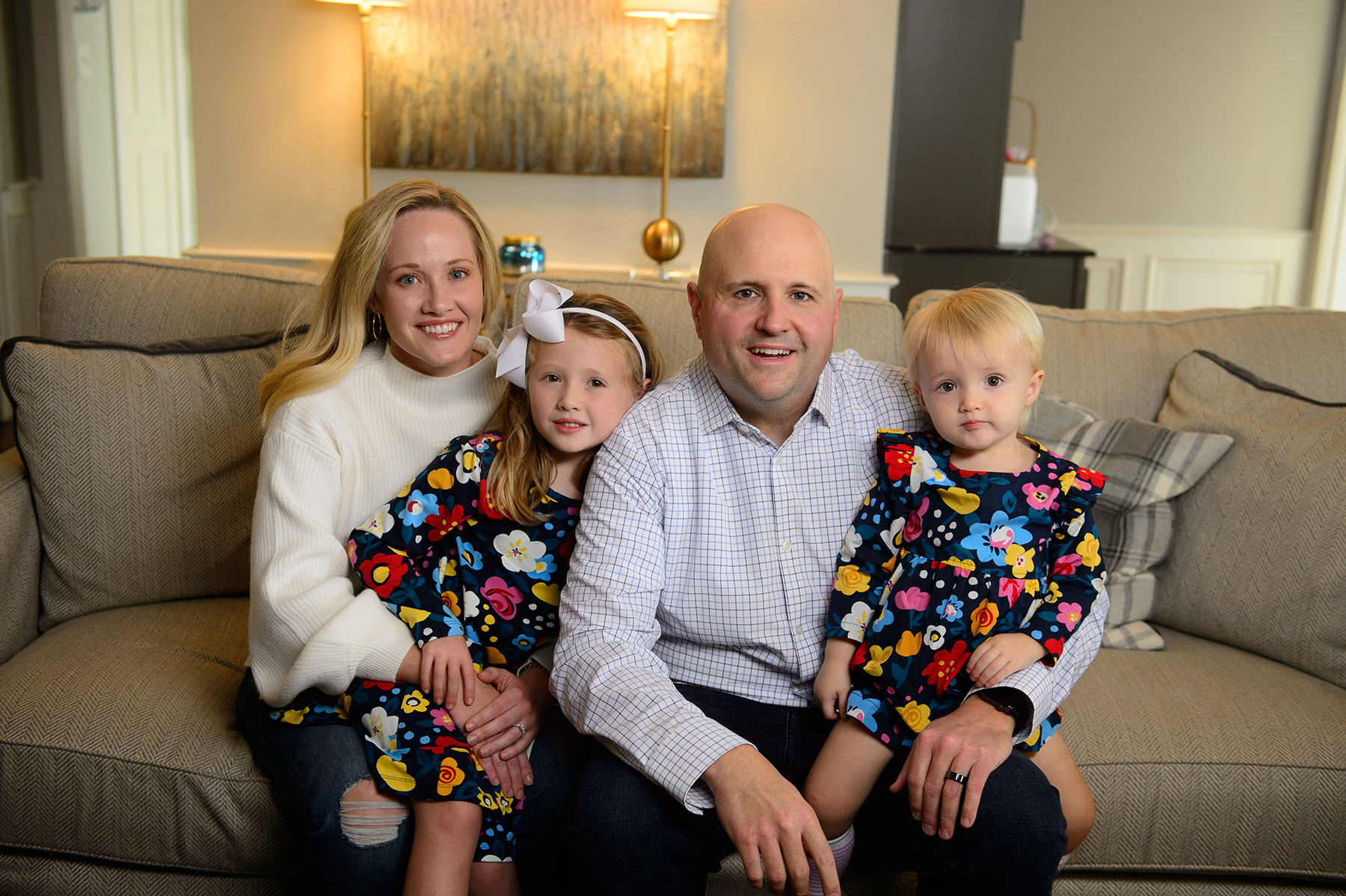 Dr. Adkins and his wife and two little girls smile for a family photo on the couch.
