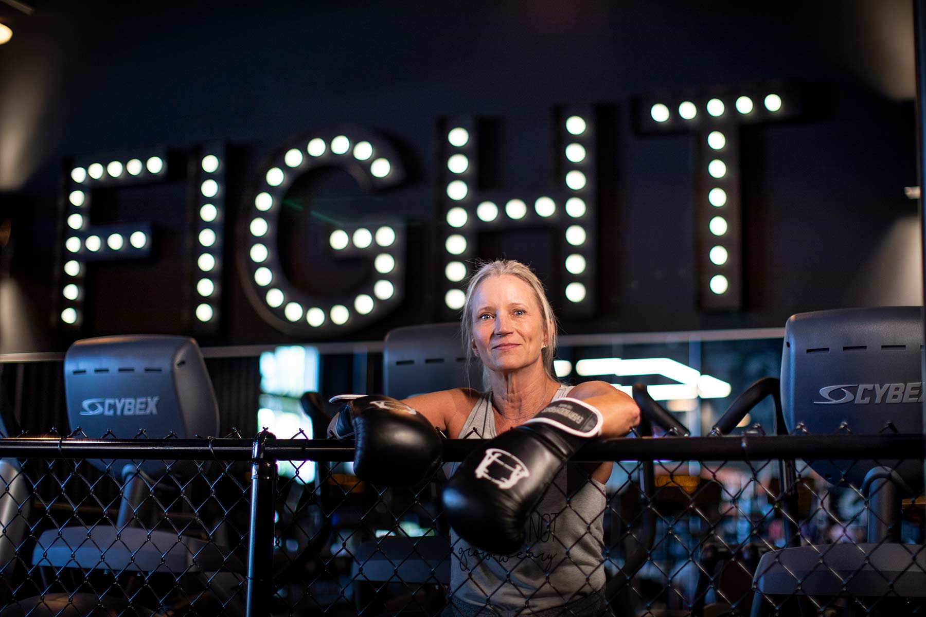 Lindi wears boxing gloves and rests on a chain link fence in front of large light up letters spelling the word FIGHT behind her.