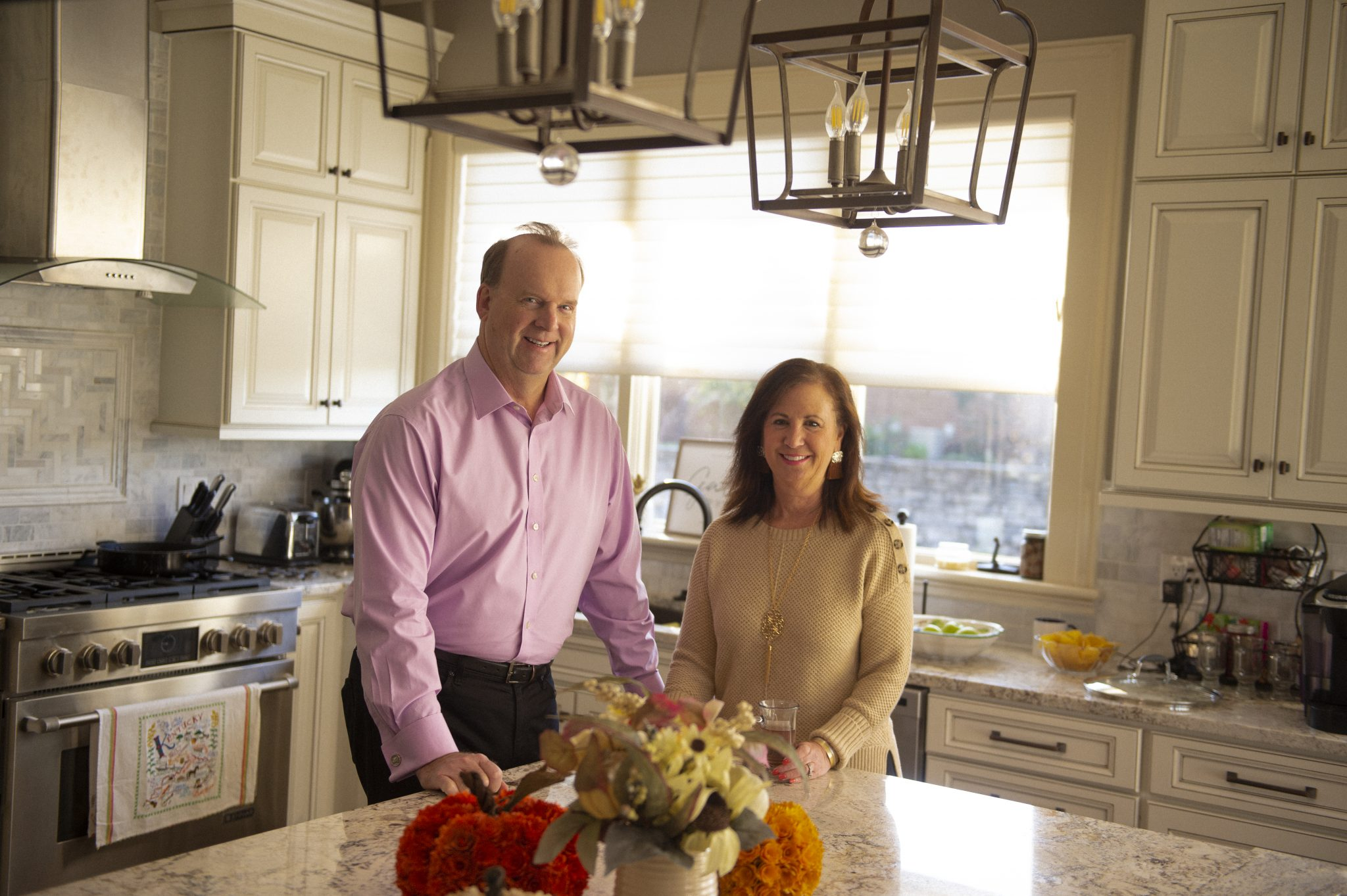 Mark Mead and his wife stand behind the kitchen island in their home.