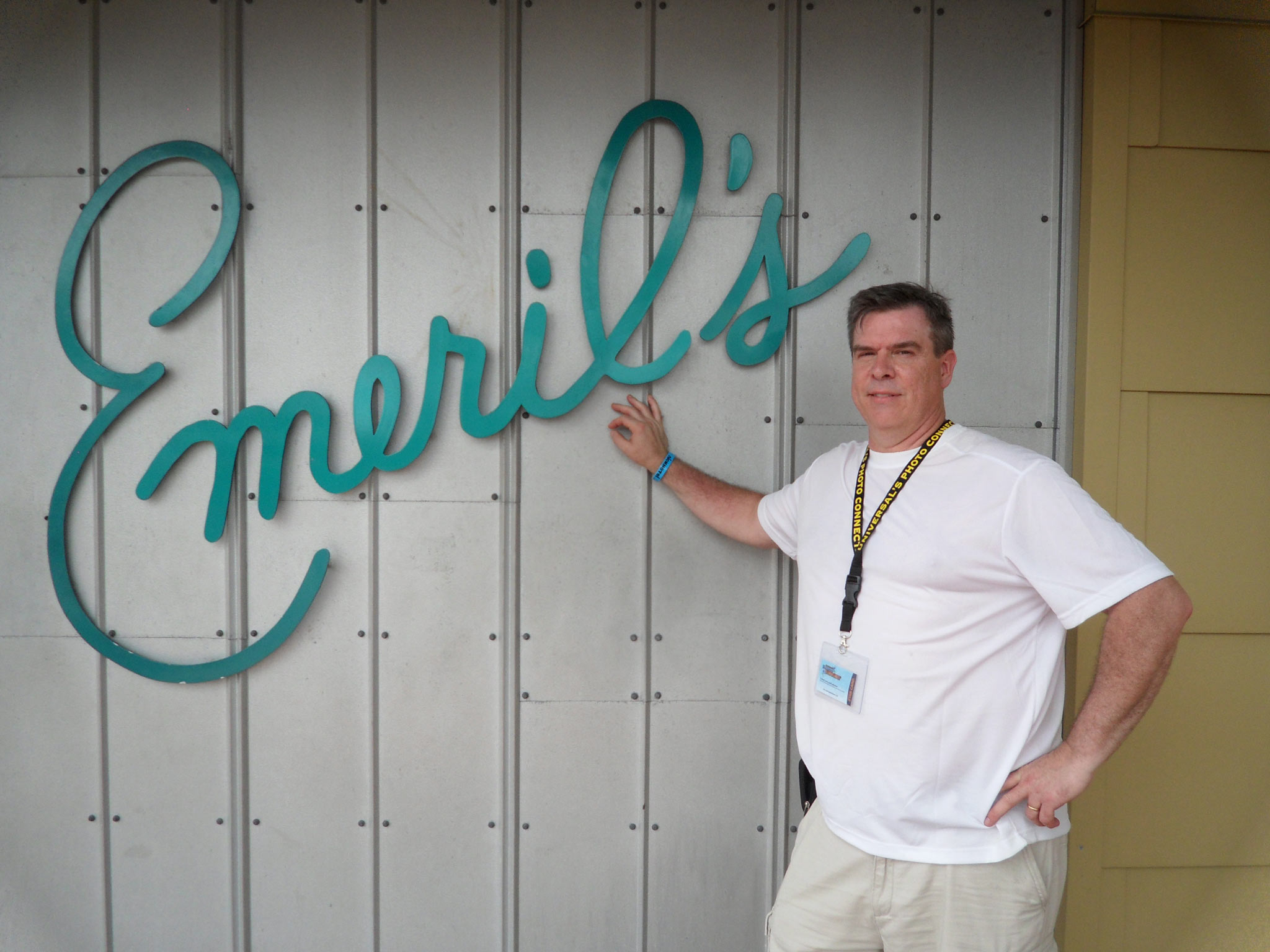 "A photo of Fred leaning against a wall that has an ""Emeril's"" sign before he joined the DPP and lost weight."