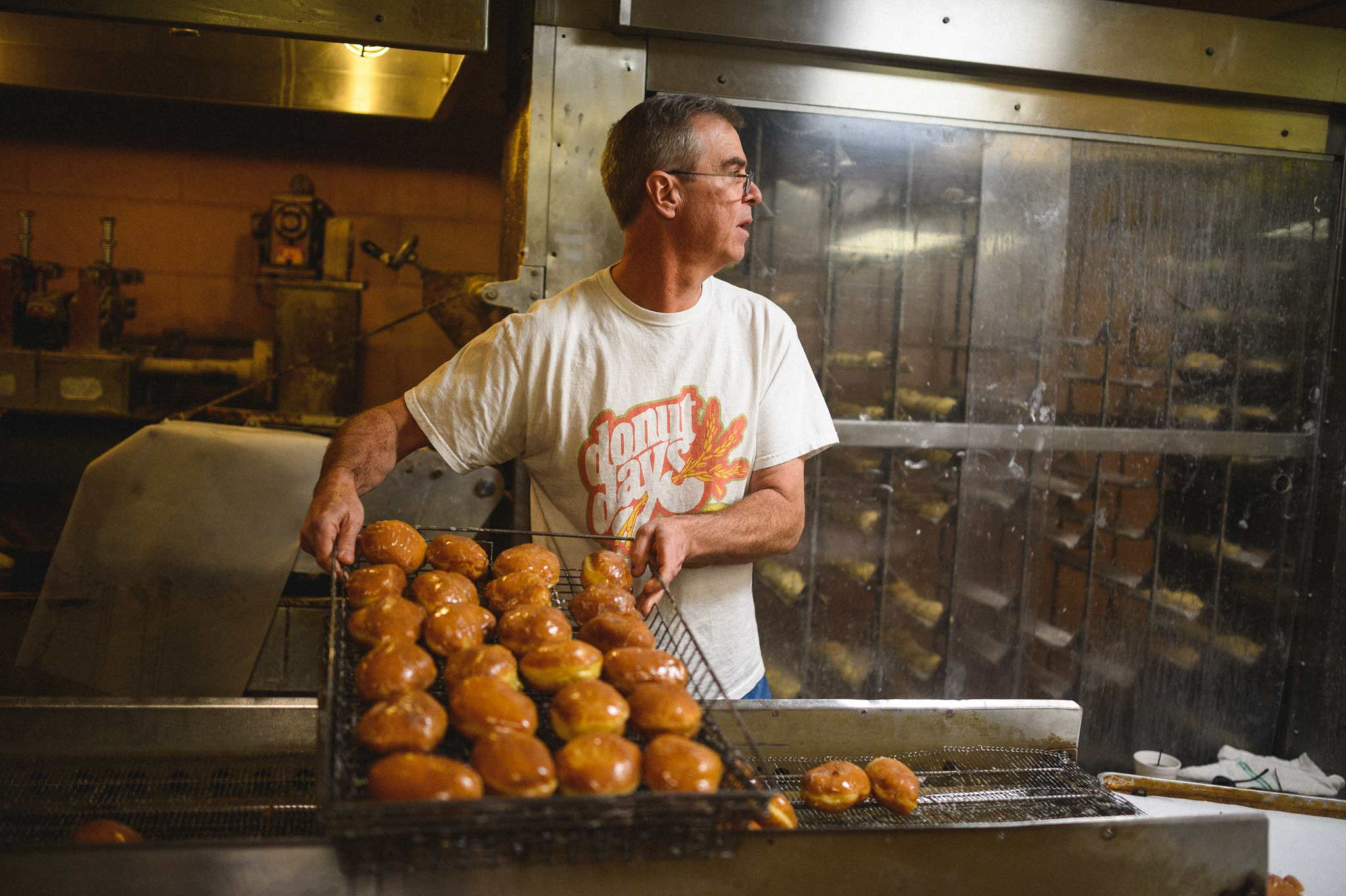 Fred takes a fresh batch of donuts off the glazing machine.