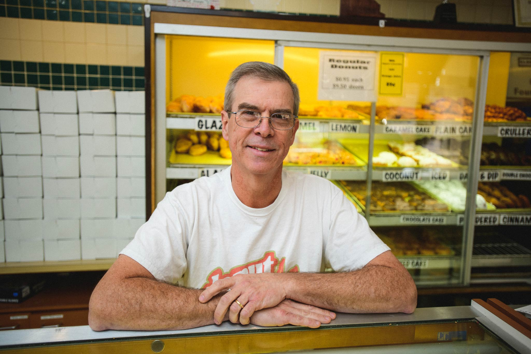 Fred Wohlstein leans against a counter at the doughnut shop and smiles.
