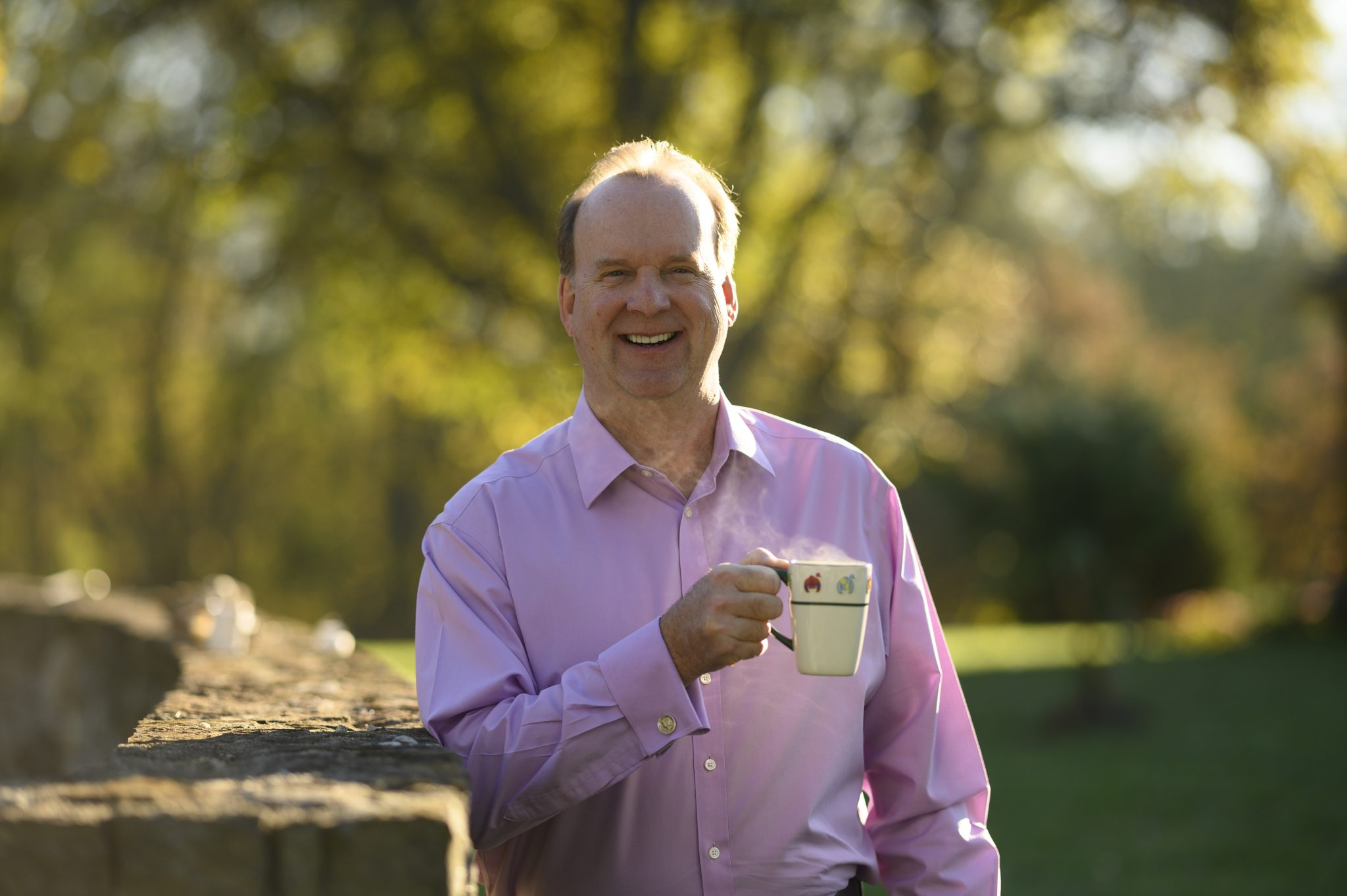 Mark Meade smiles and enjoys a steaming cup of coffee outside.