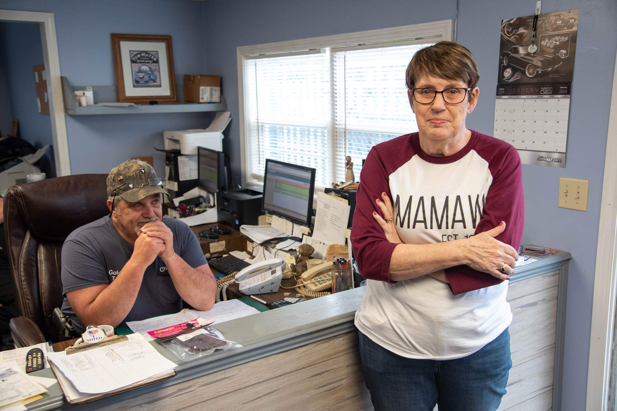 Debbie leans against the Gold City Towing office reception desk while Chuck sits in the chair behind her and smiles.