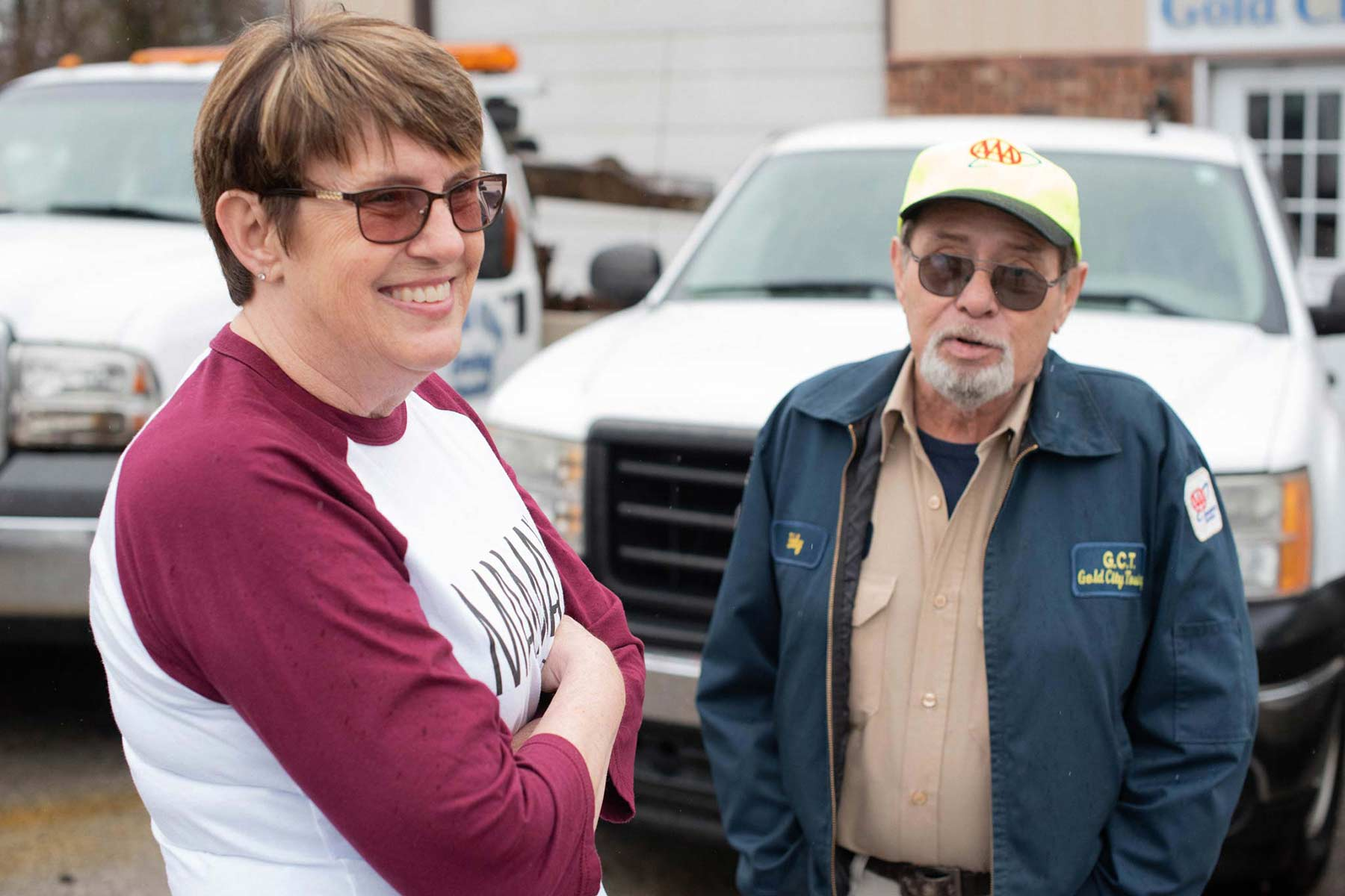 Debbie crosses her arm and smiles in the parking lot of her family's towing business with her husband beside her.