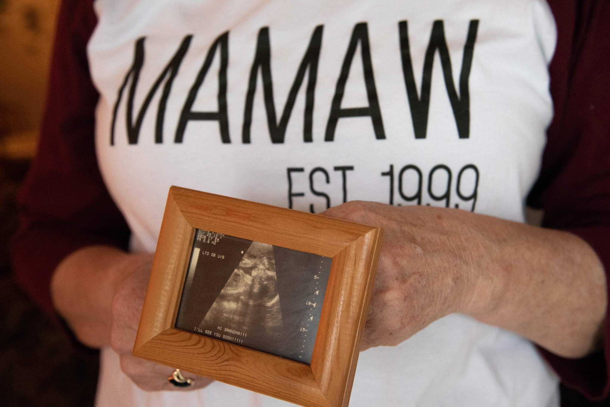 Debbie holds a framed photo of the sonograph of her granddaughter.