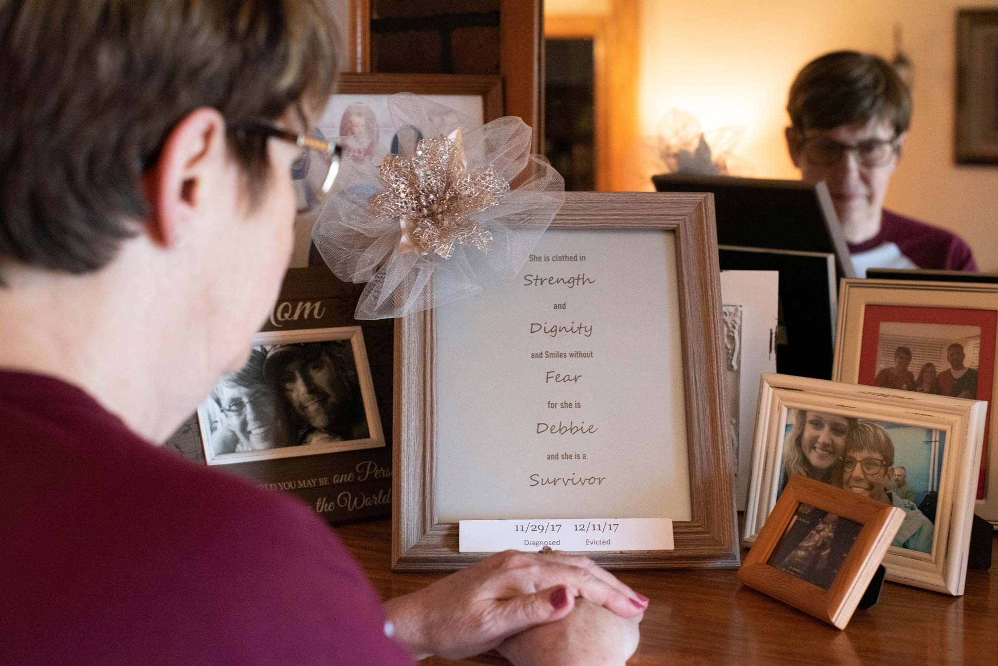 "Debbie pauses for a moment in front of a bunch of framed photographs. She's looking at a framed print that says ""She is clothed in Strength and Dignity and Smiles without Fear for she is Debbie and she is a Survivor""."