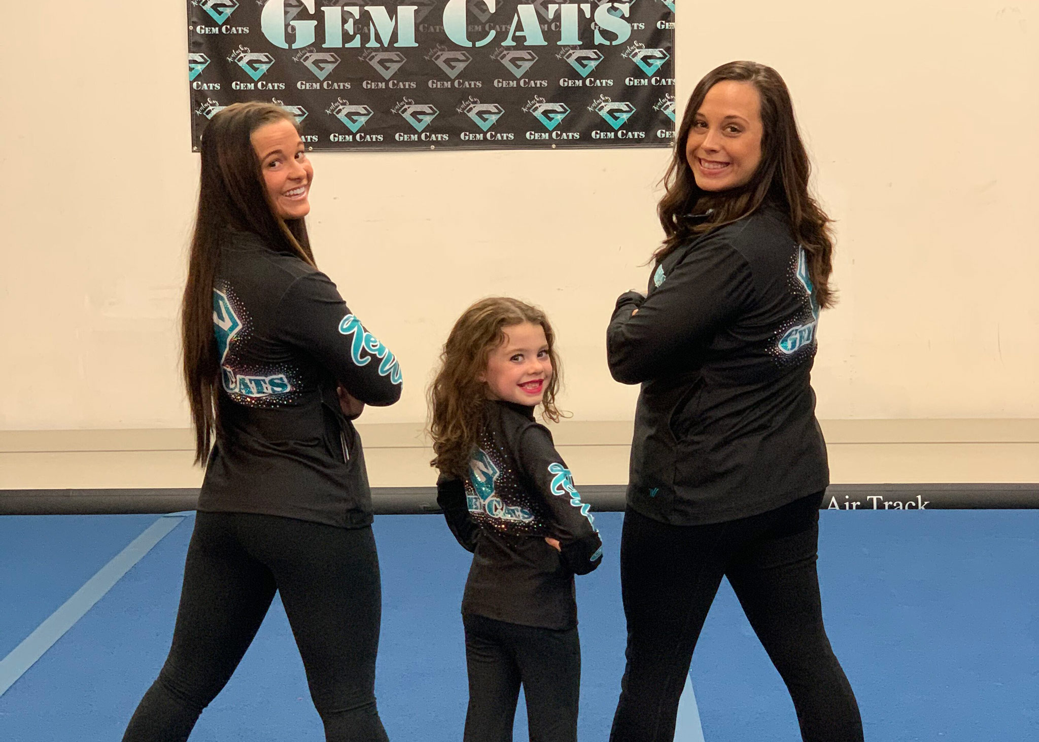 Izzy poses with two of the adult Gem Cat gymnasts.