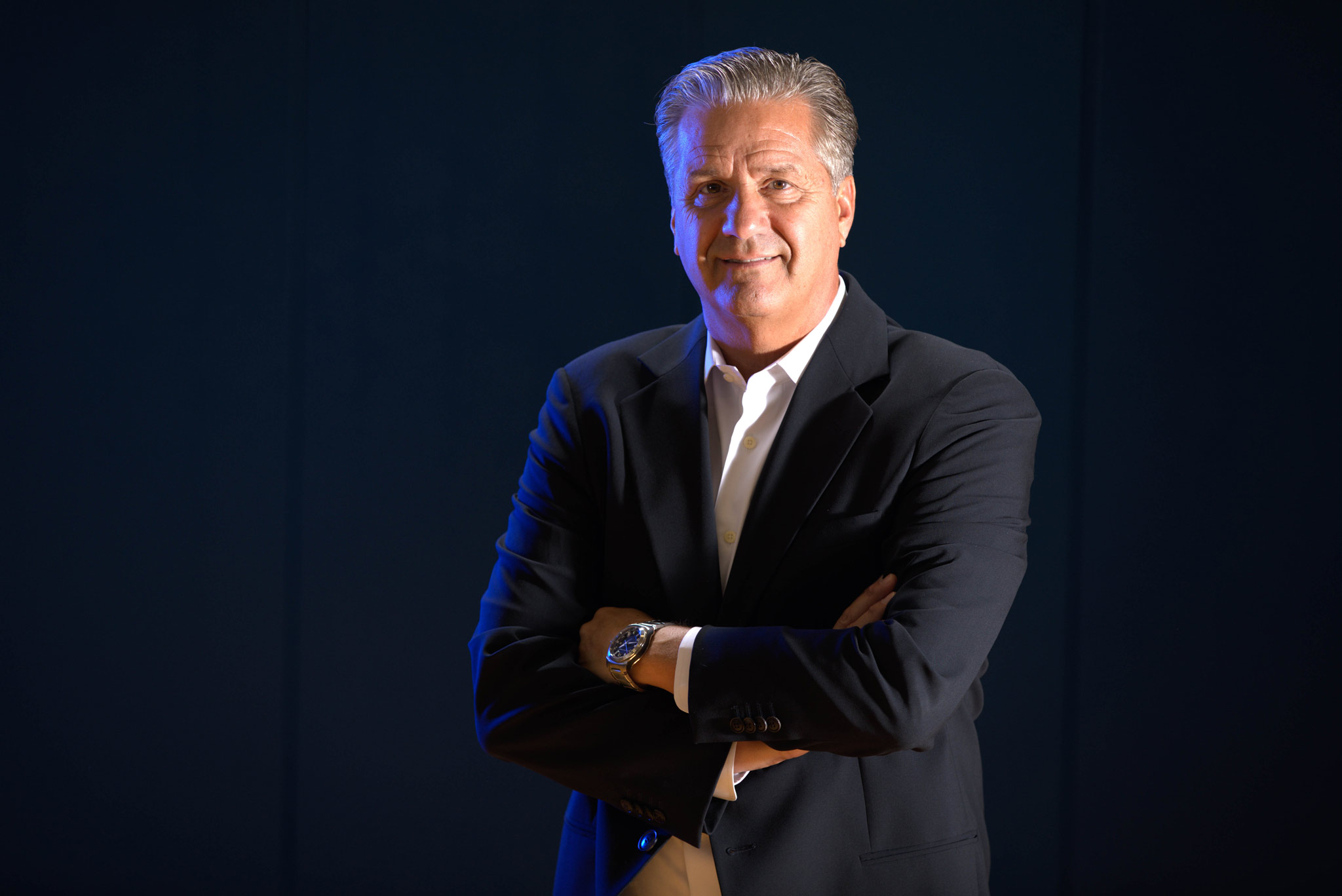 Coach Calipari wears a suit and poses for a portrait.