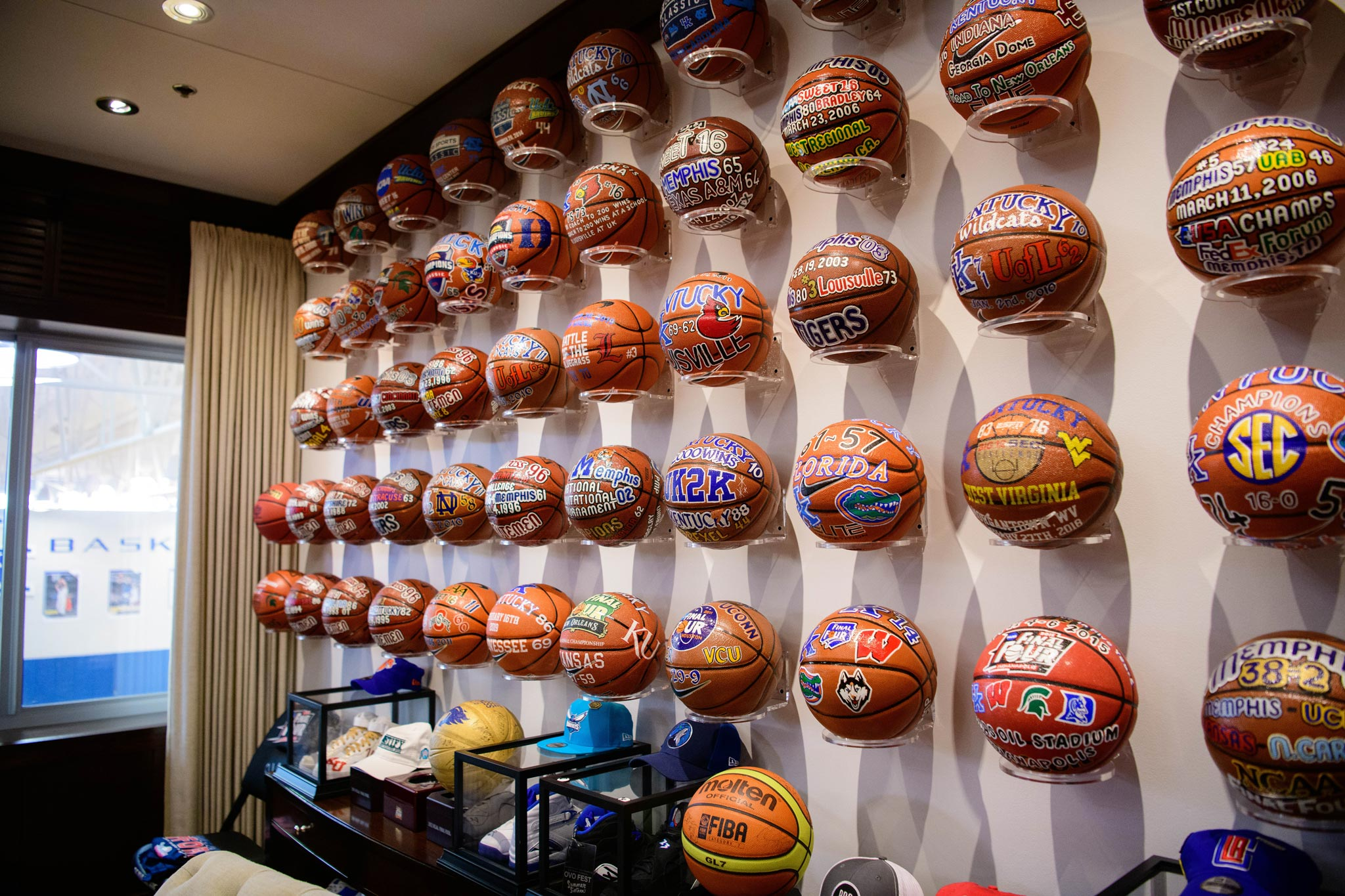 A wall covered in display mounts with championship basketballs.