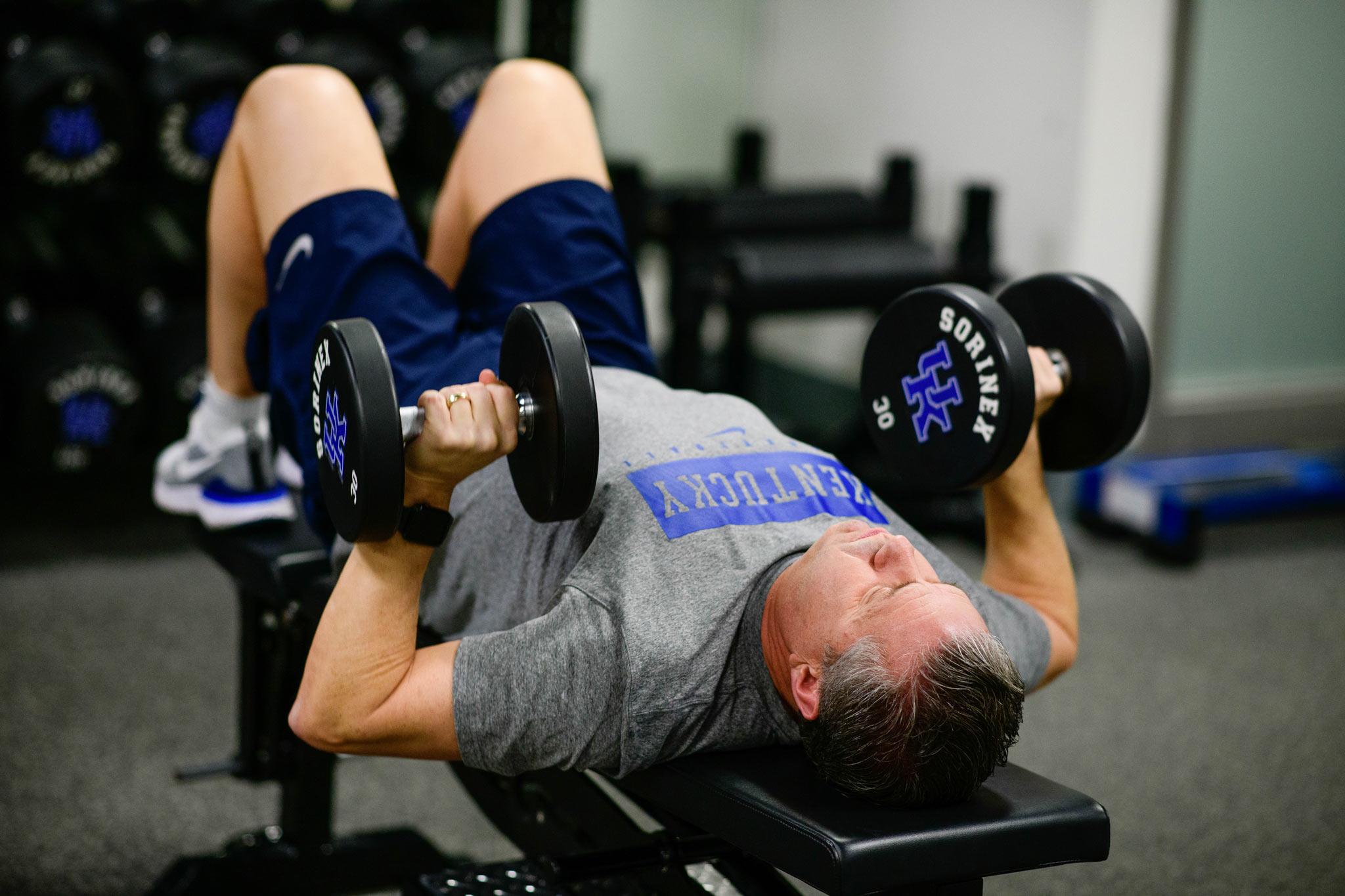Coach Calipari bench presses 30 pound dumbbells.