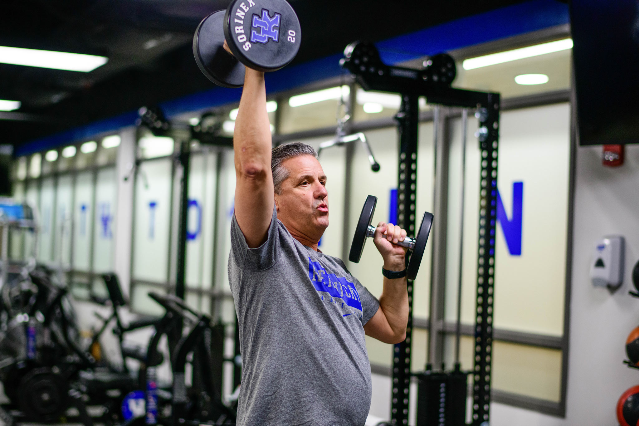 Coach Calipari lifts 20 pound dumbbells over his head at the gym.