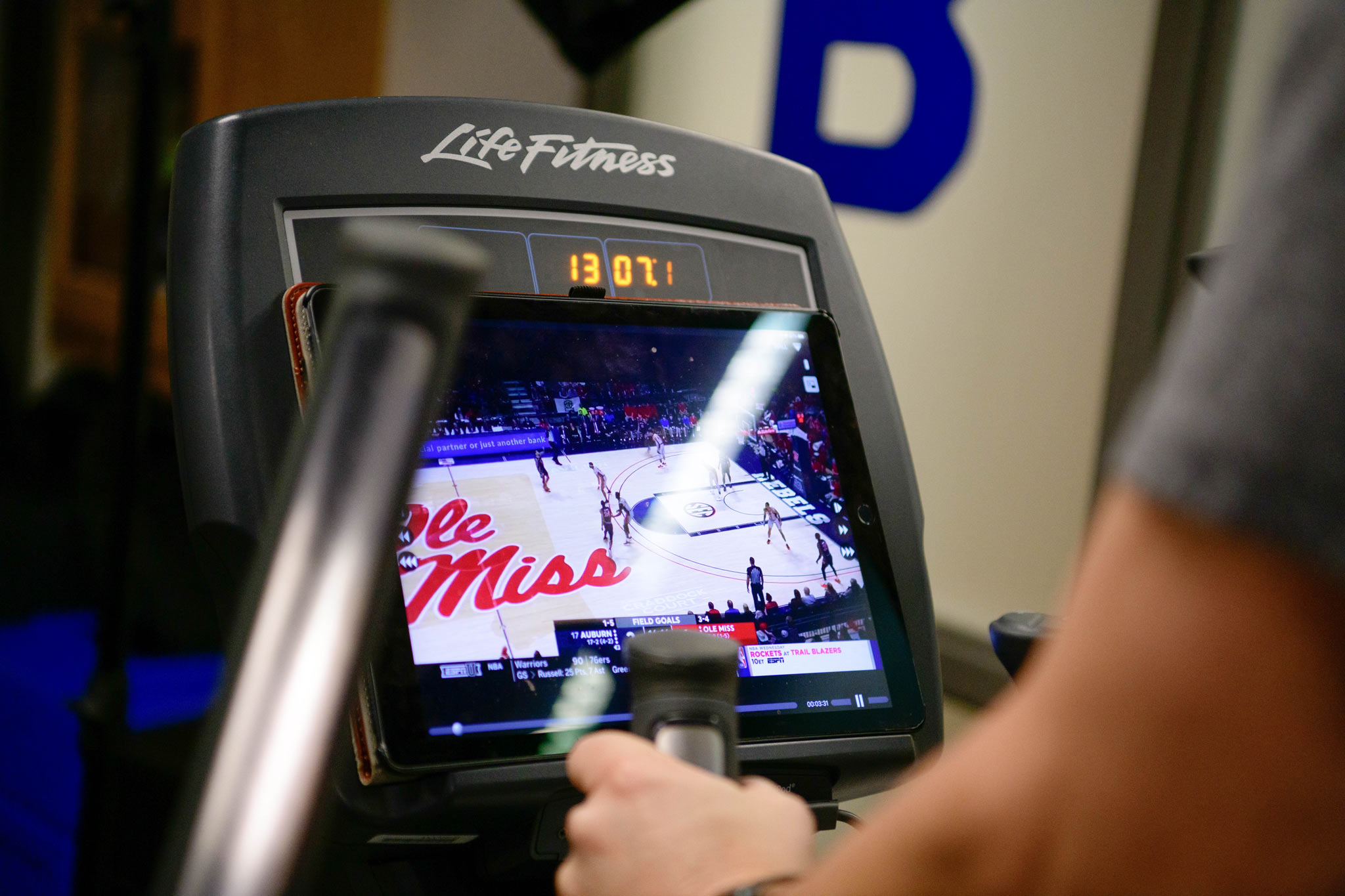 Coach Calipari rests his iPad against the elliptical's console to watch basketball games while he works out.