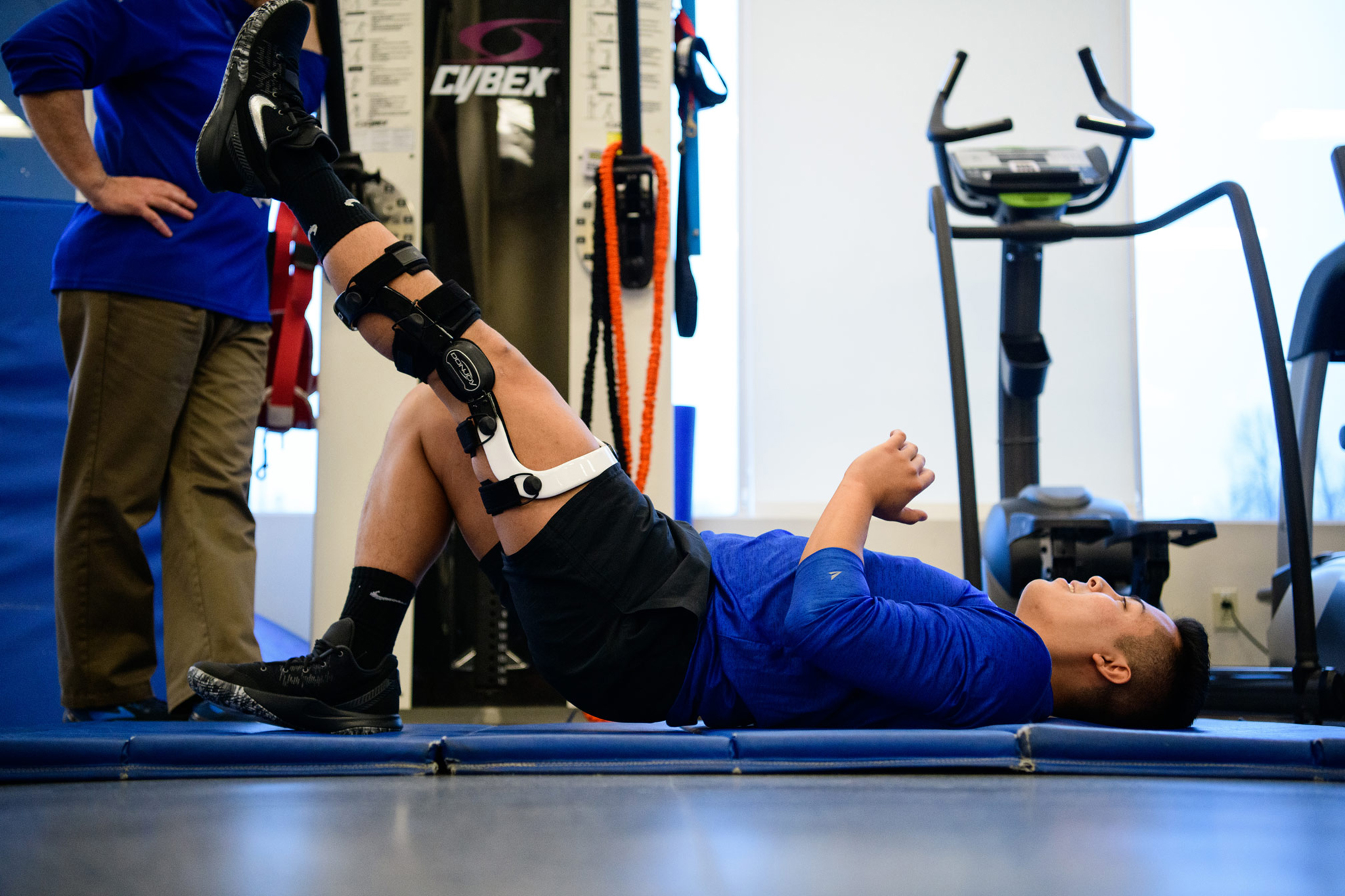 Gil wears a knee brace and lies down to perform knee strengthening exercises.