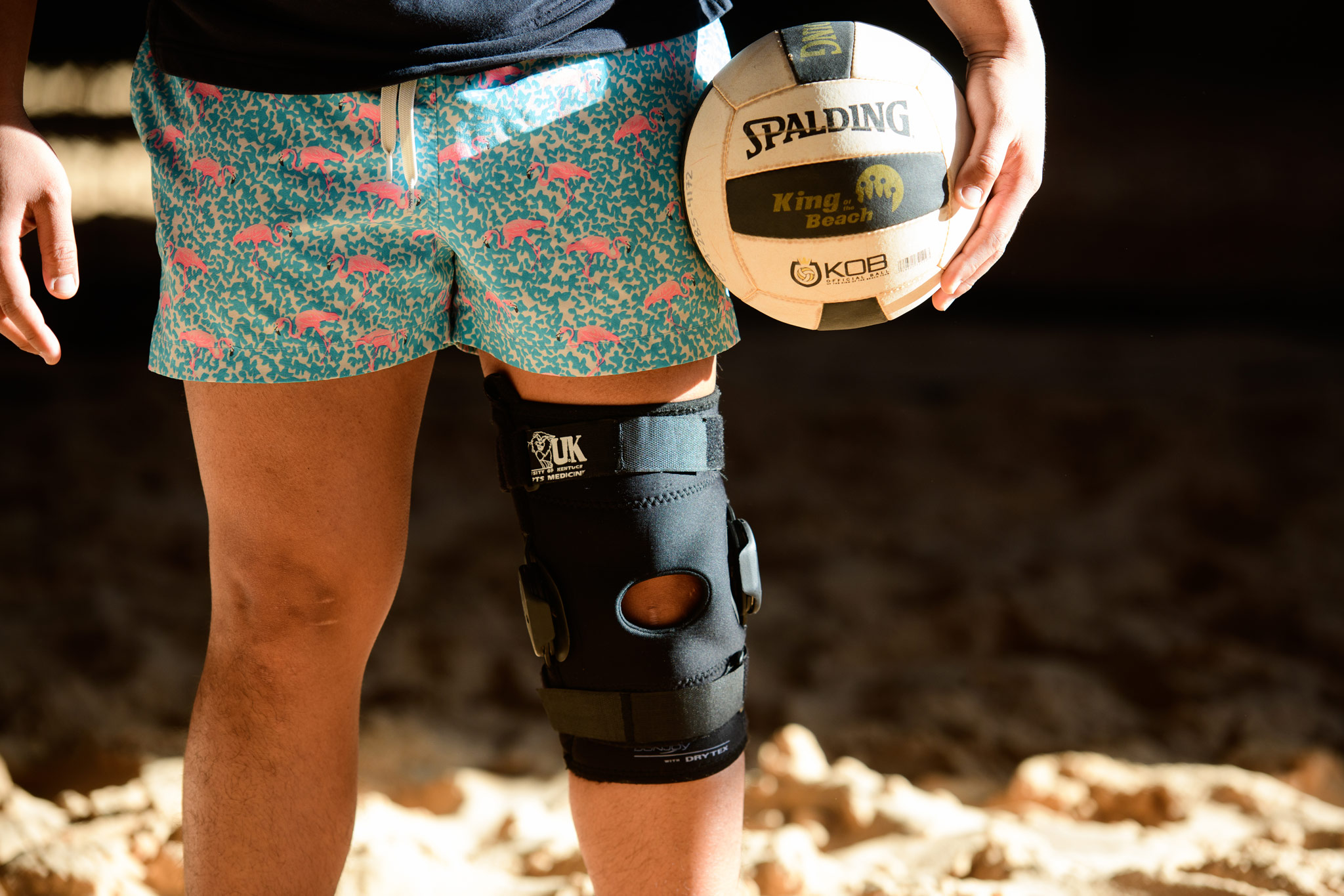 Gil's left knee has a black knee brace over it while he holds a volleyball against his left hip.
