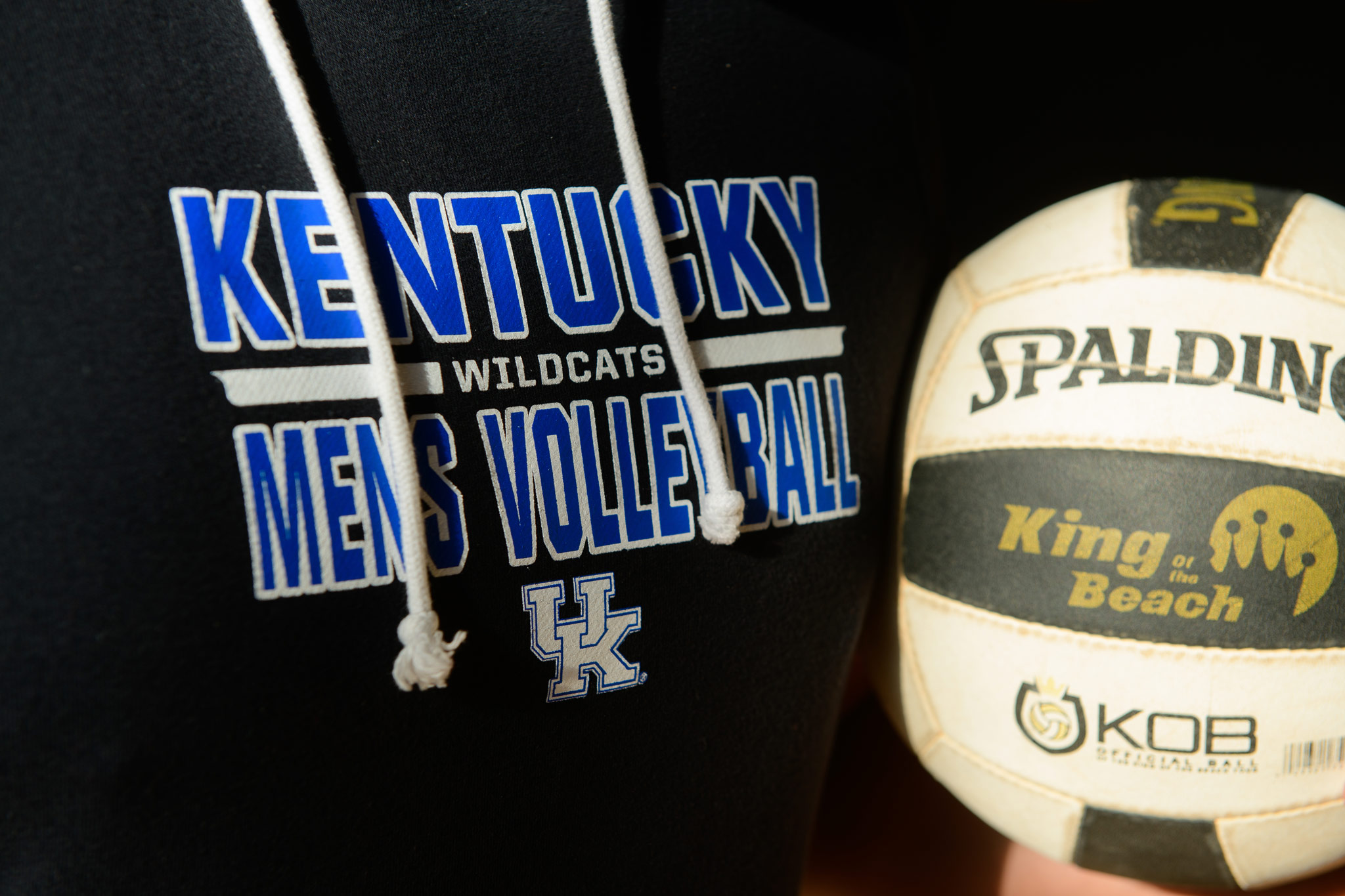 Close up of Gil's Kentucky Wildcats Men's Volleyball sweatshirt and Spalding volleyball.