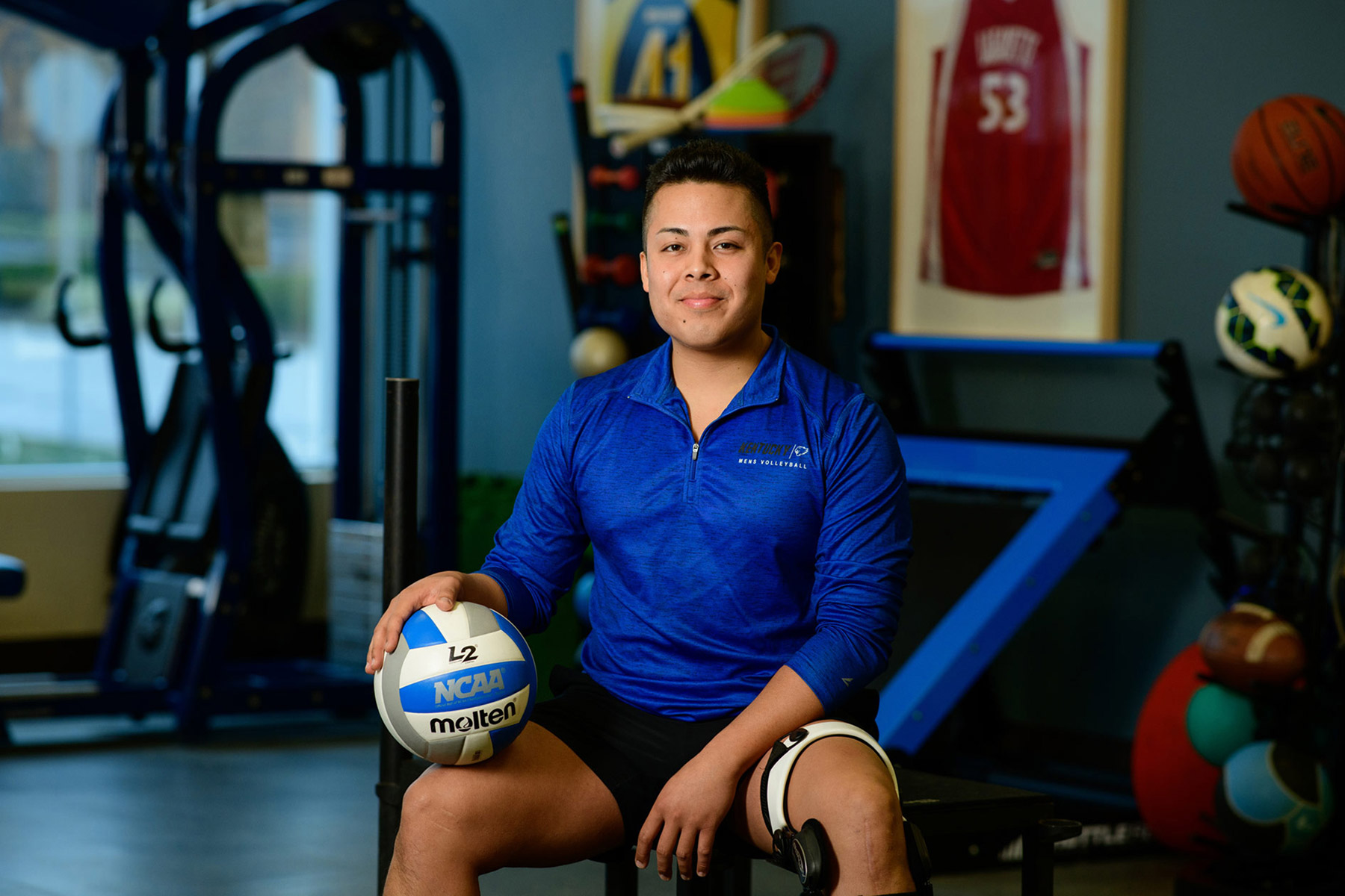Gil Bagang sits on a bench at his physical therapist's office with a volleyball resting on his knee.