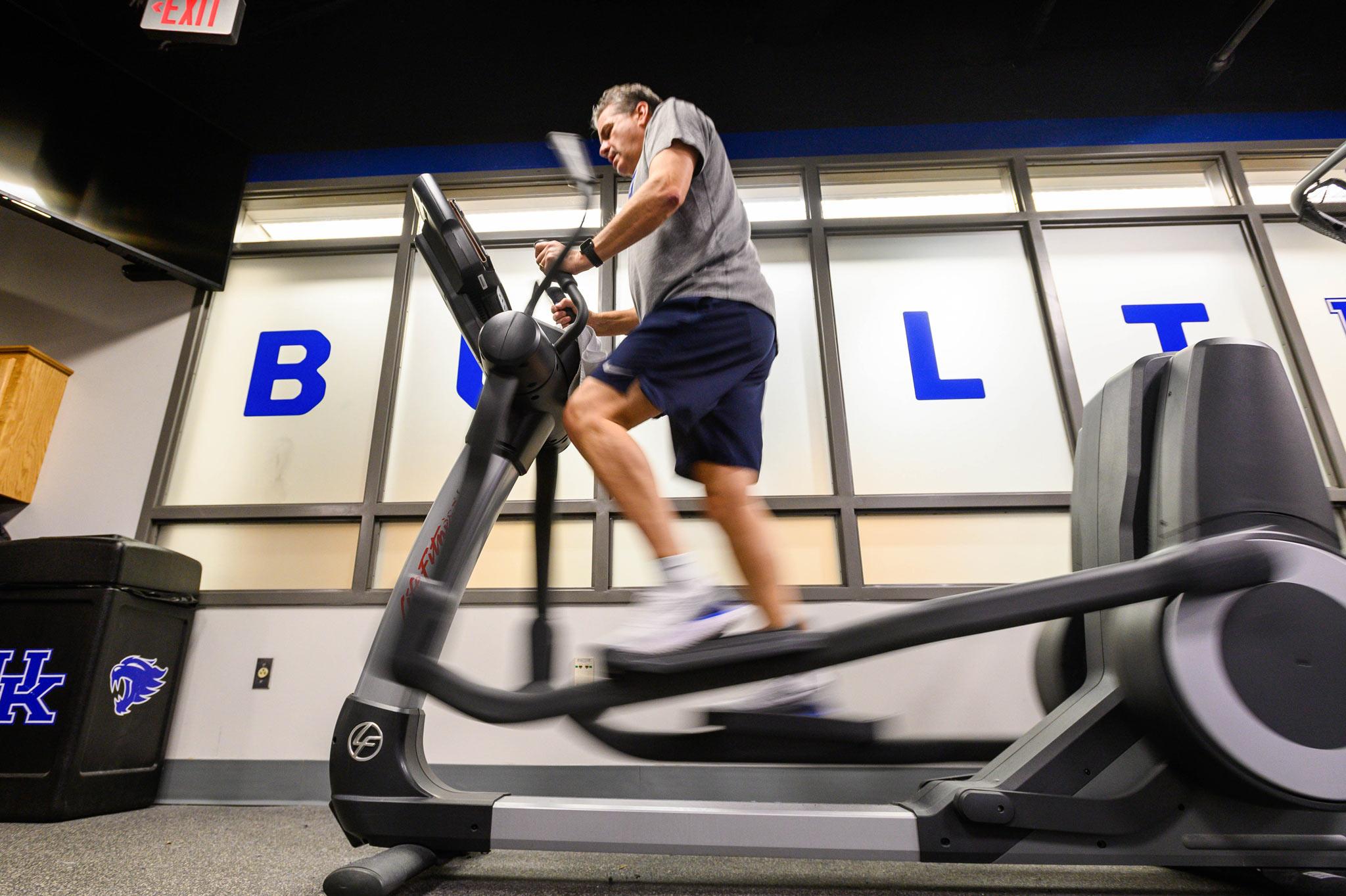Coach Calipari works out on an elliptical machine.