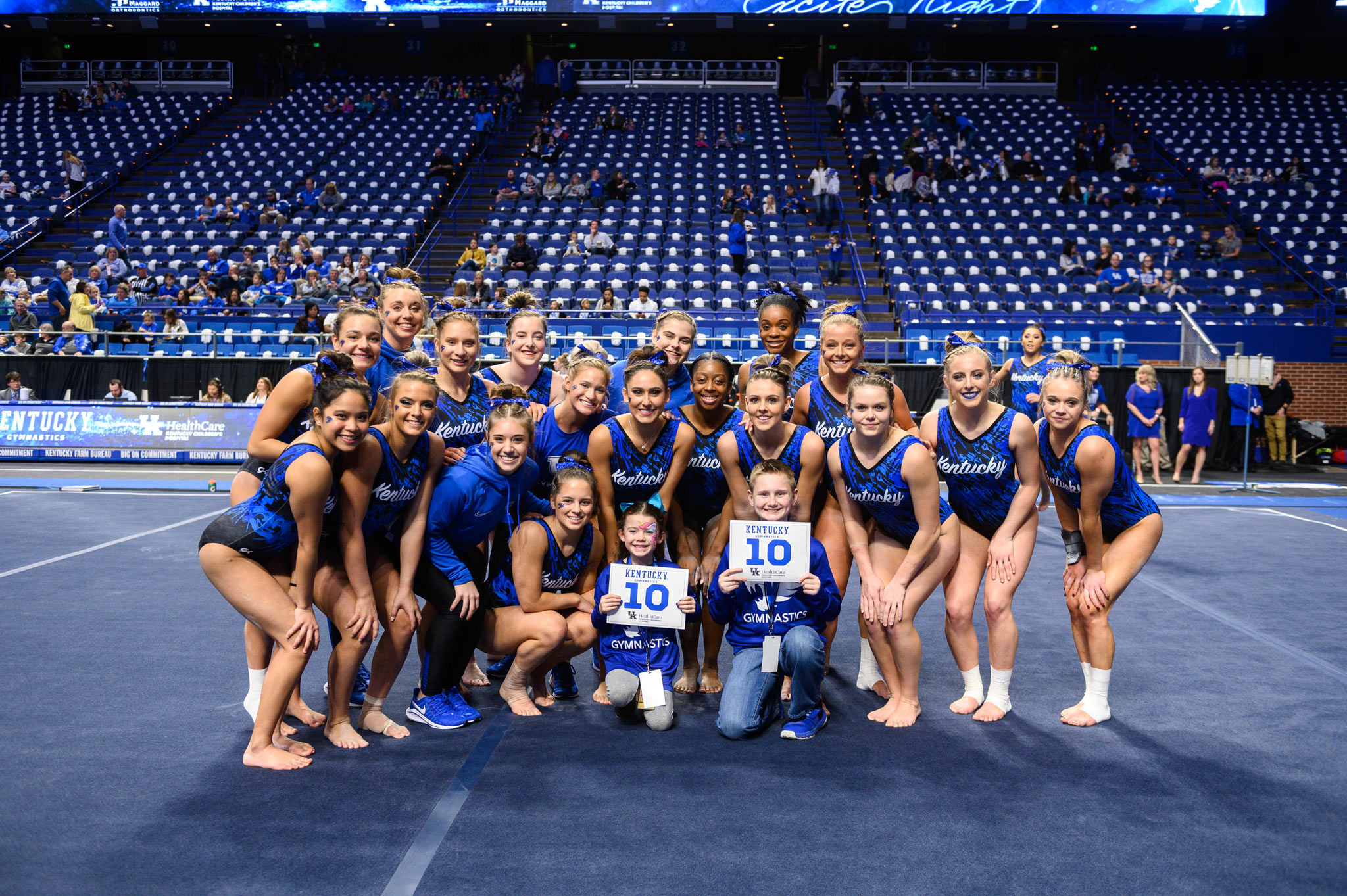 Izzy and Dalton hold signs with 10's on them and kneel in front of a group of UK gymnasts.