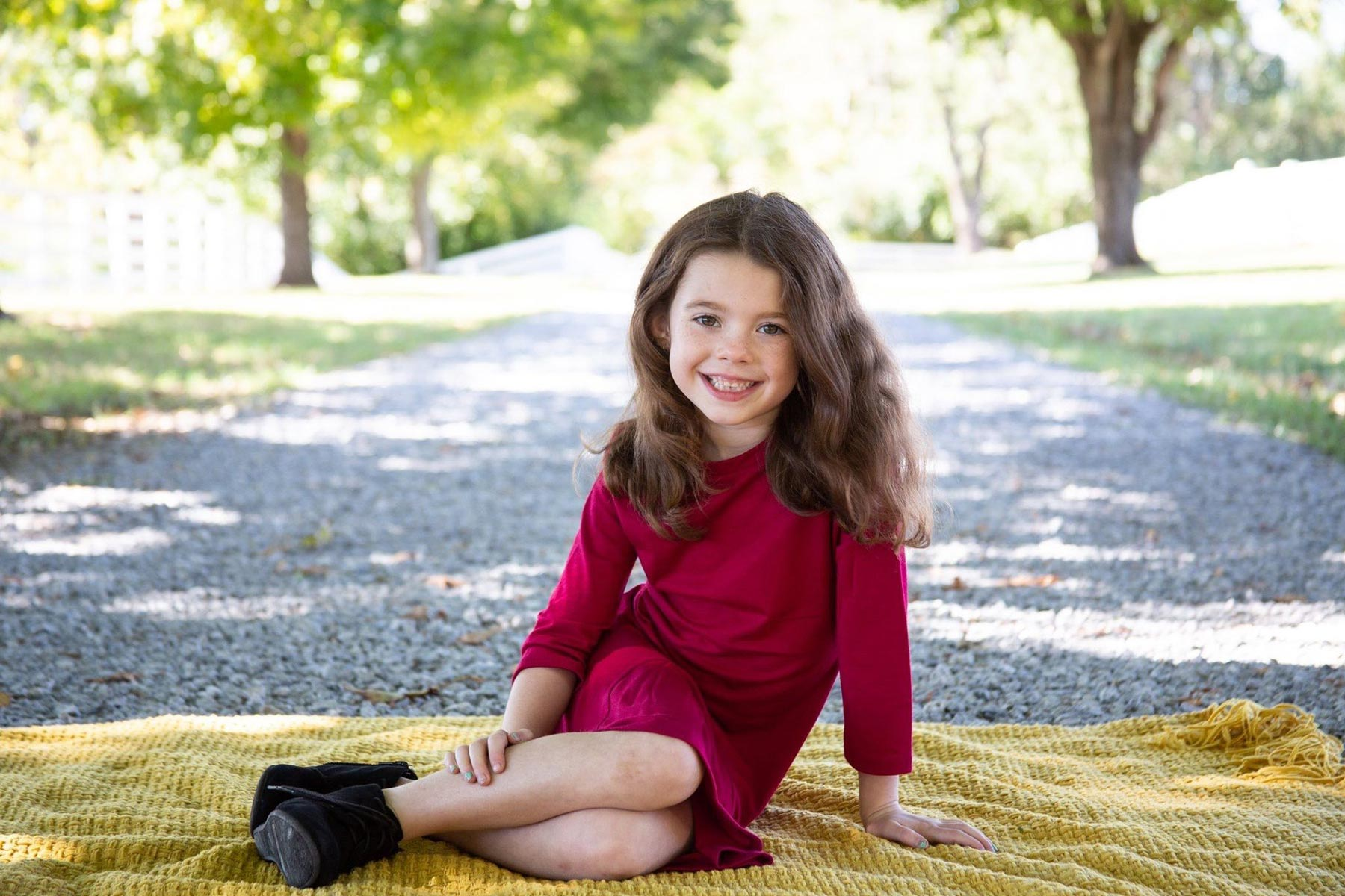 Izzy leans on one arm while sitting on a yellow blanket in her driveway and smiles.