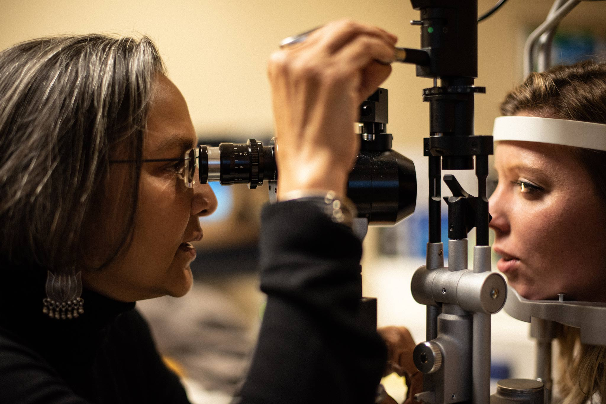 Dr. Capoor looks through a slit lamp into a patient's eyes.