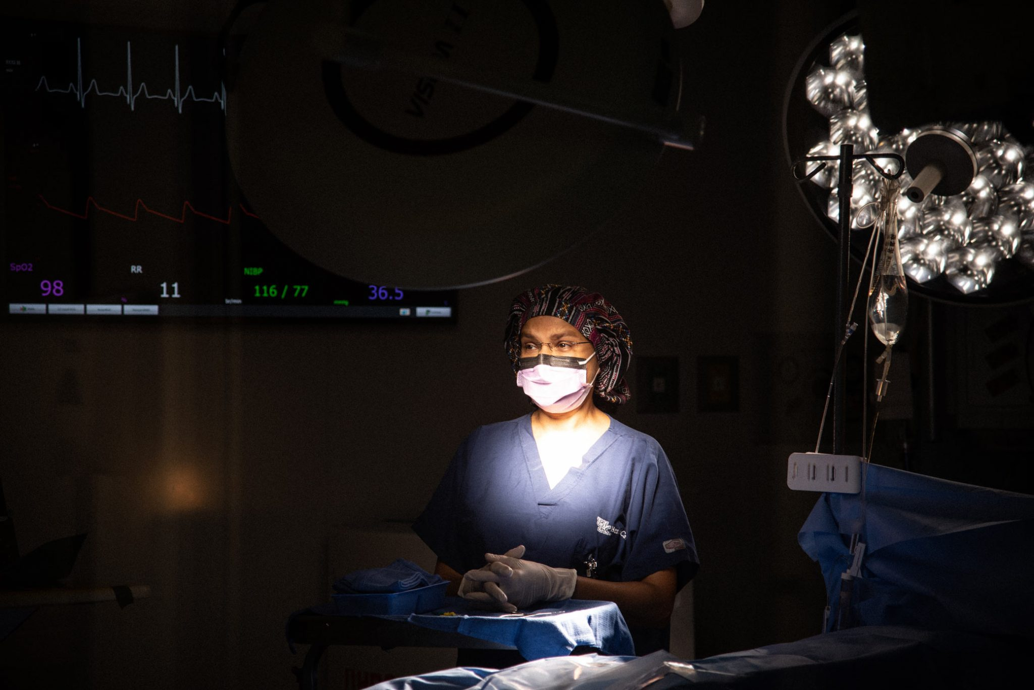 Dr. Capoor stands in a dim operating room with a light shining on her.