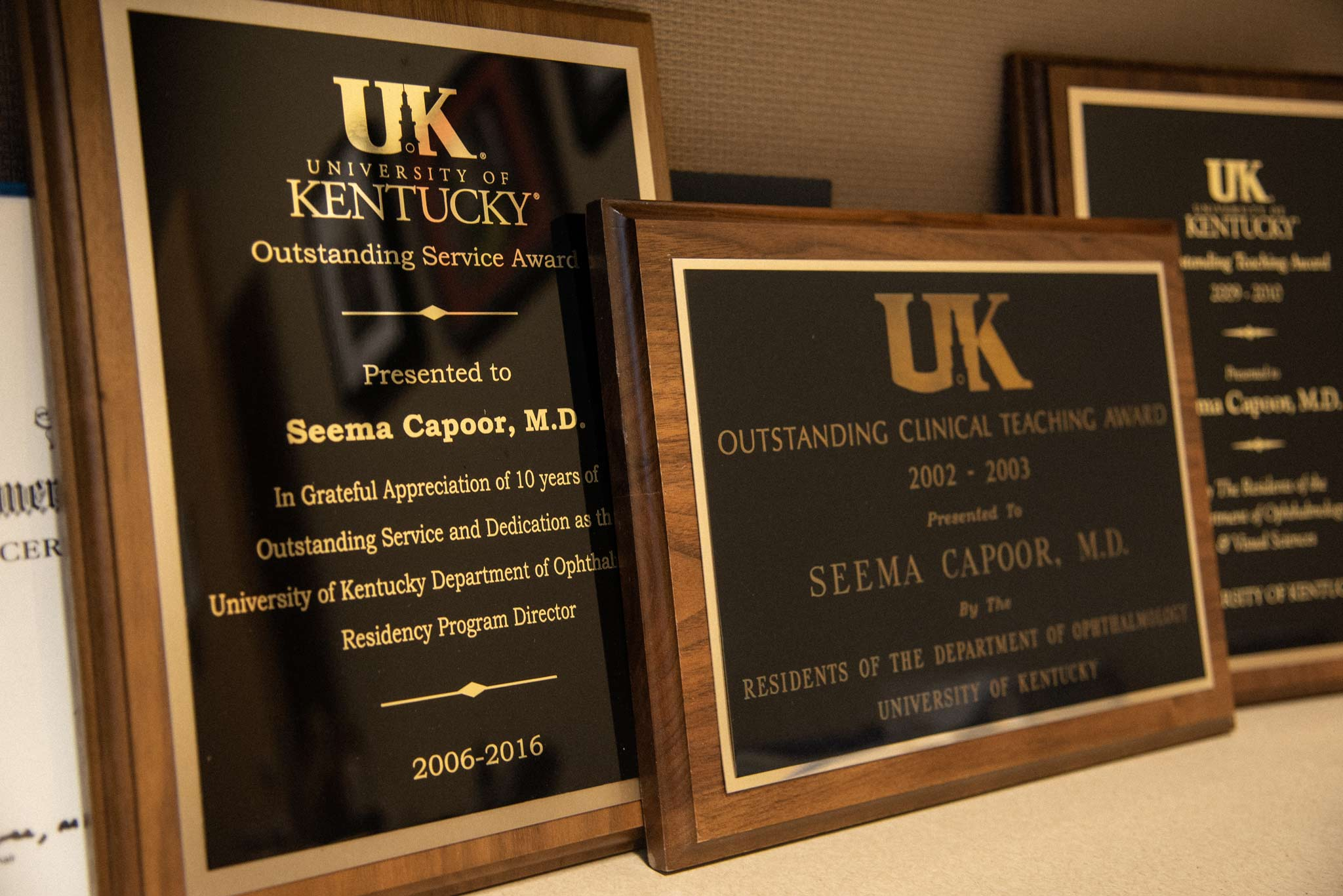 A close up of several award plaques Dr. Capoor has earned.