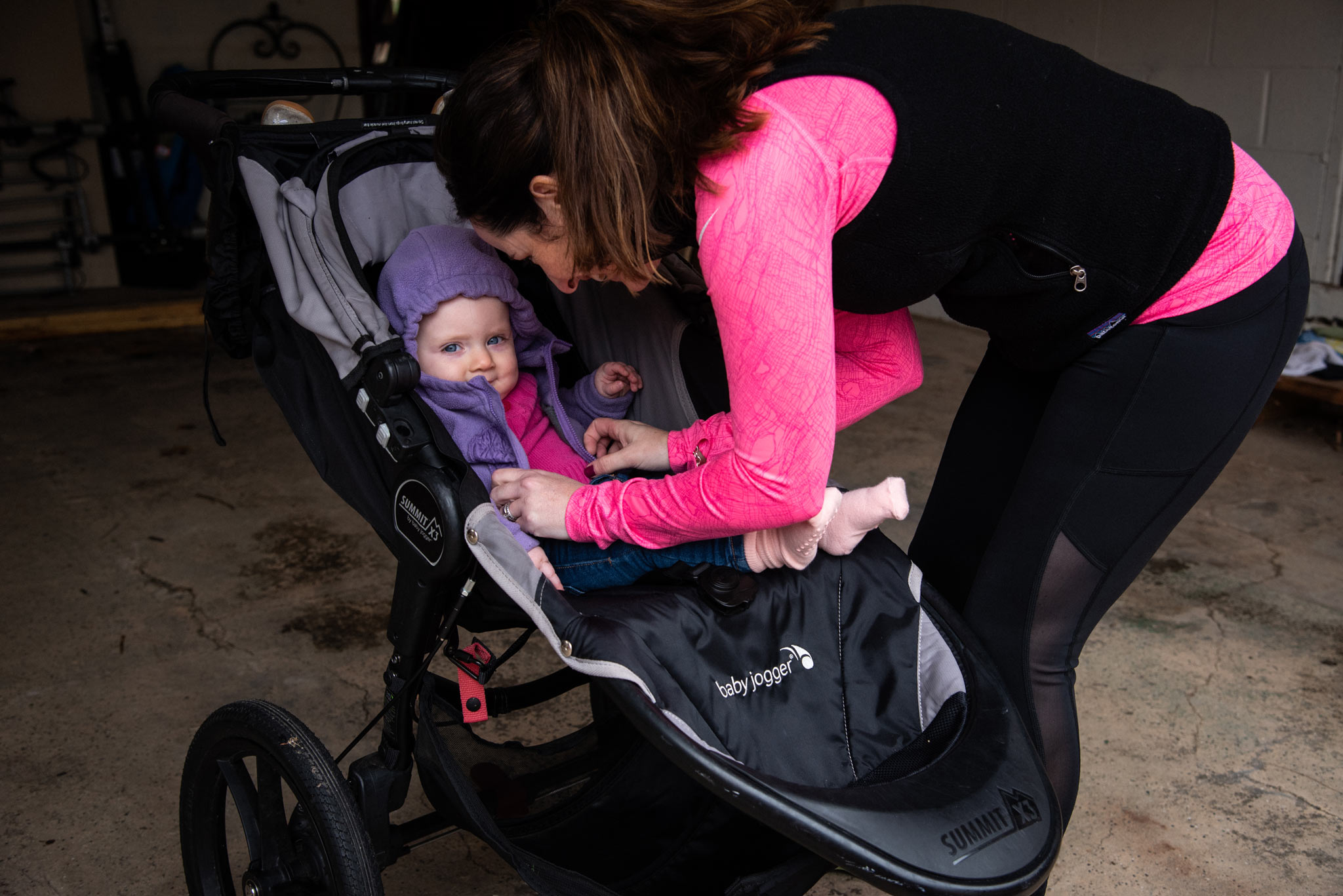 Amberlee buckles Anna in her stroller before going for a jog.