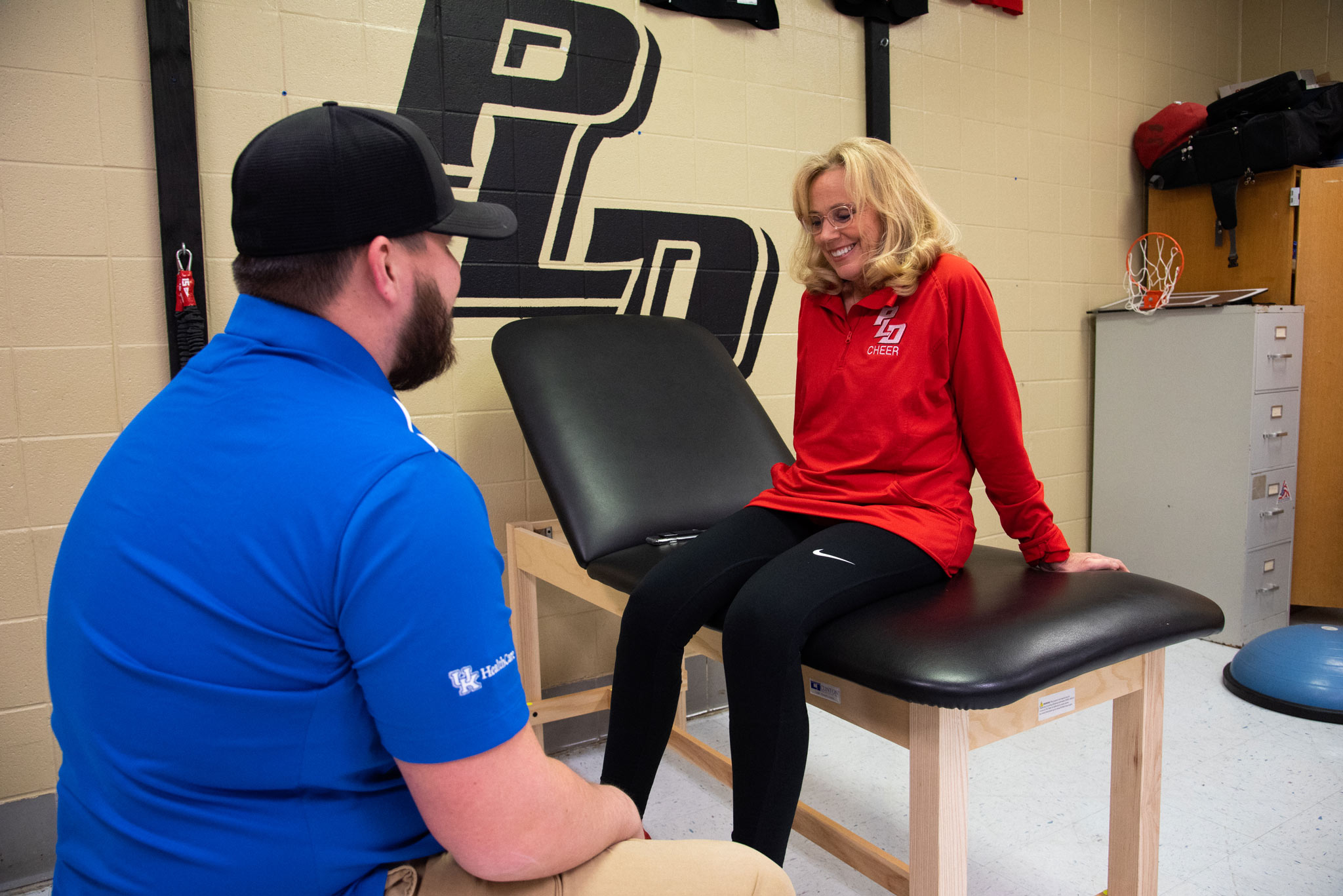 Donna sits on a patient's bench while her physical therapist talks to her about her knee.