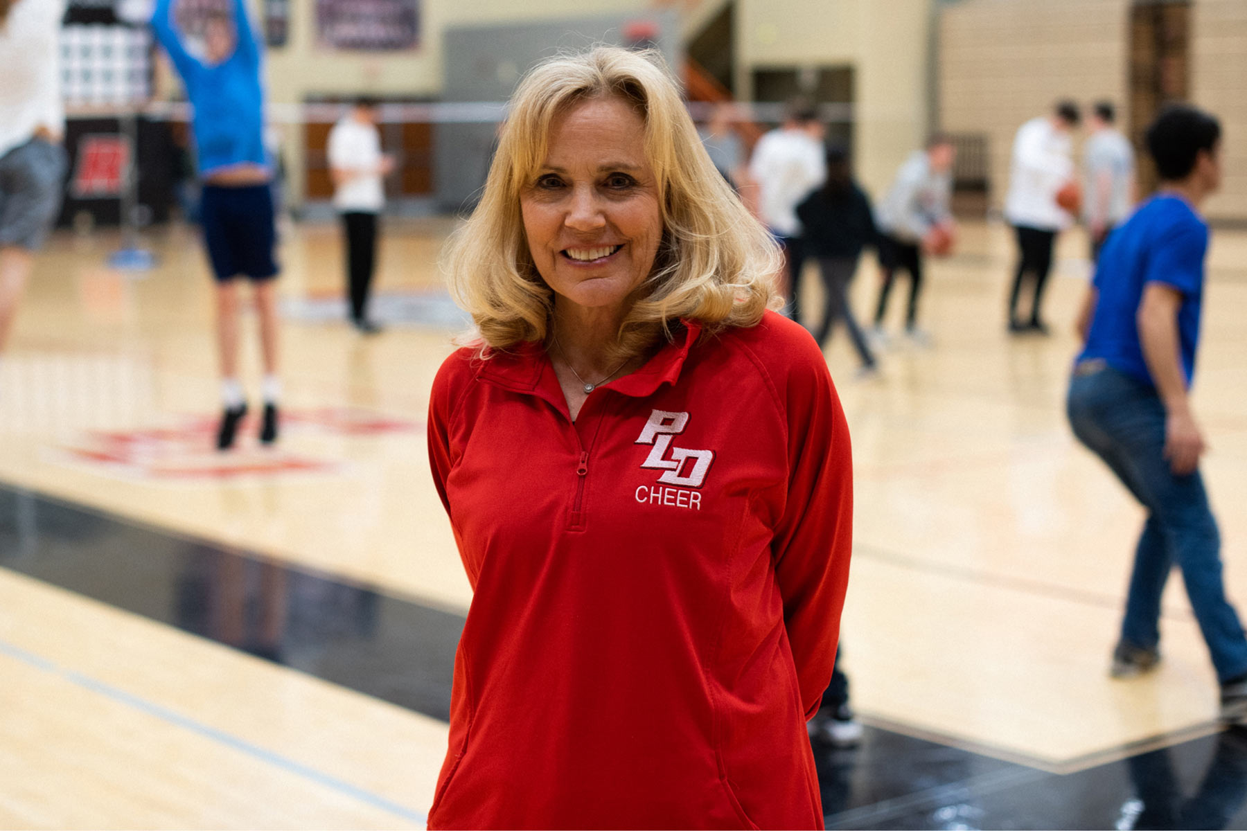 Donna Martin wears her PLD cheer sweatshirt and smiles in a busy gymnasium.
