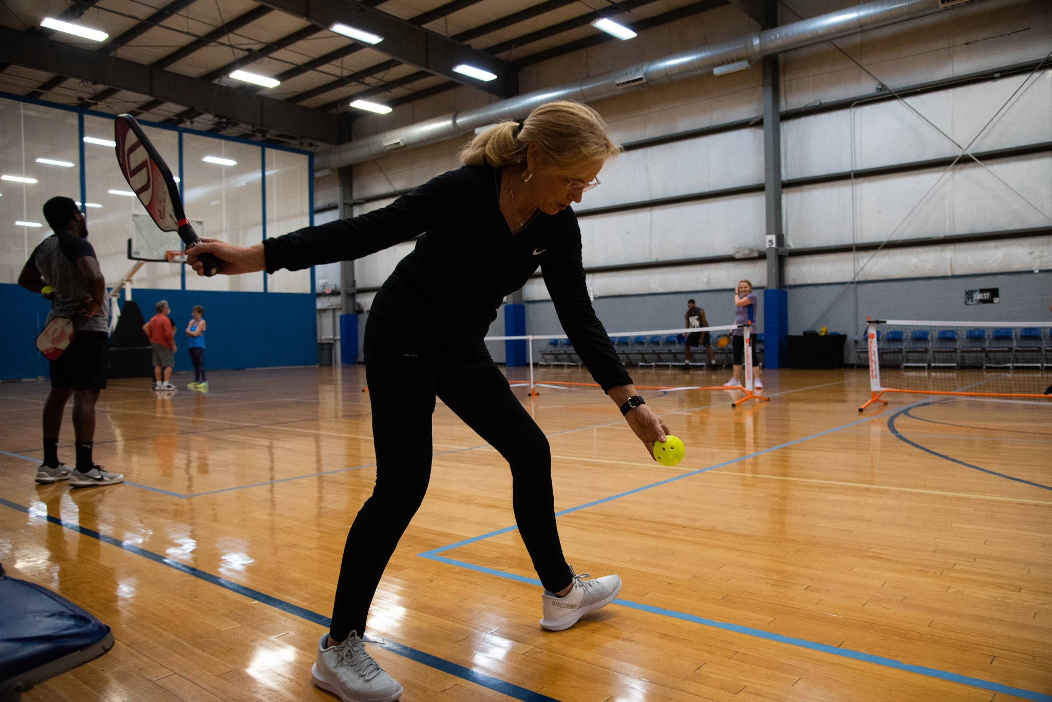 Donna prepares to serve the ball at a pickleball game.