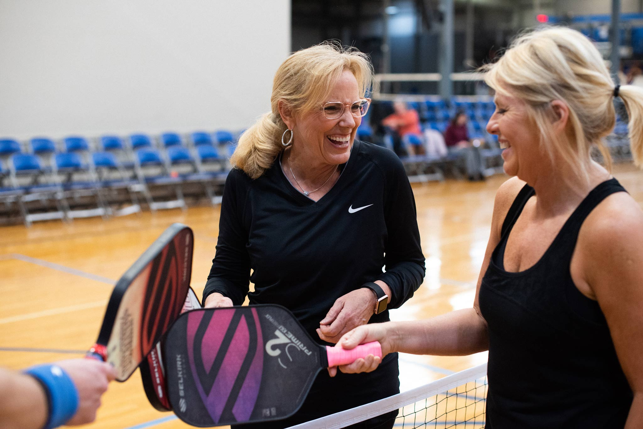 Donna smiles and laughs with a competitor on the other side of the net.
