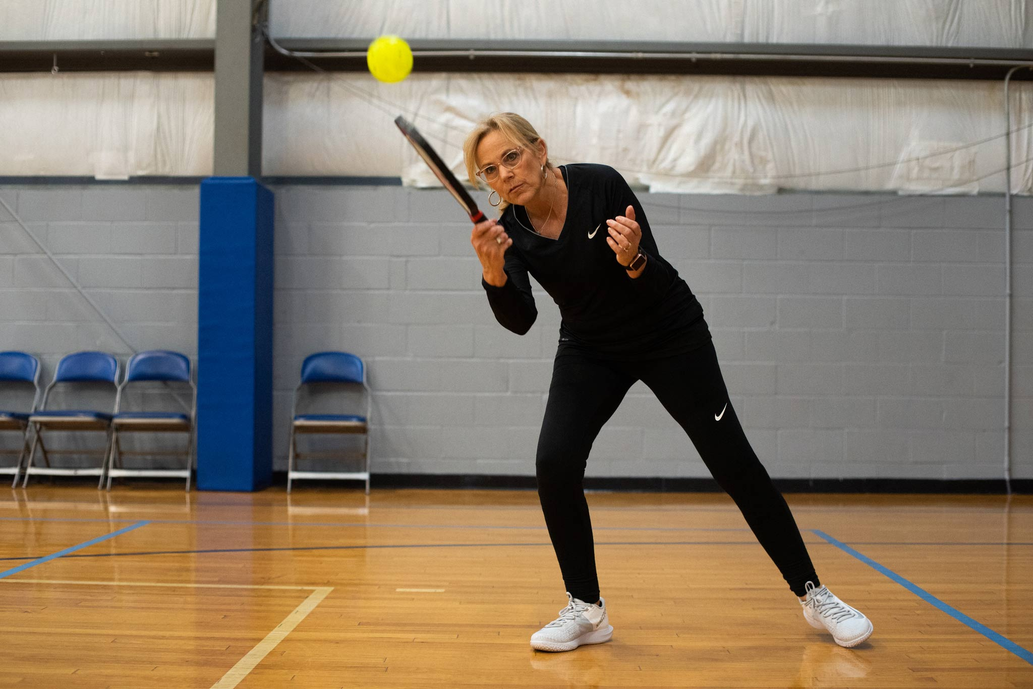 Donna leans into a swing to hit the ball back during a pickleball game.