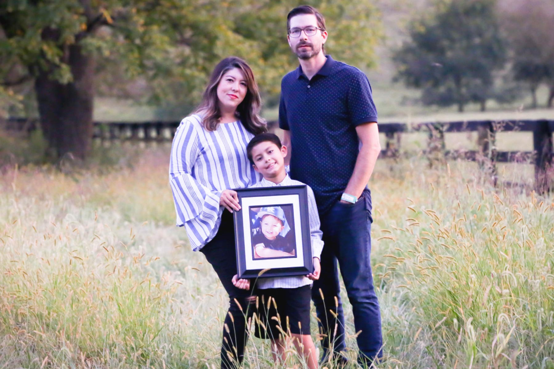 Liz, Benjamin, and Maximo stand together in a field for a family portrait. Maximo holds a large, framed portrait of Marco.