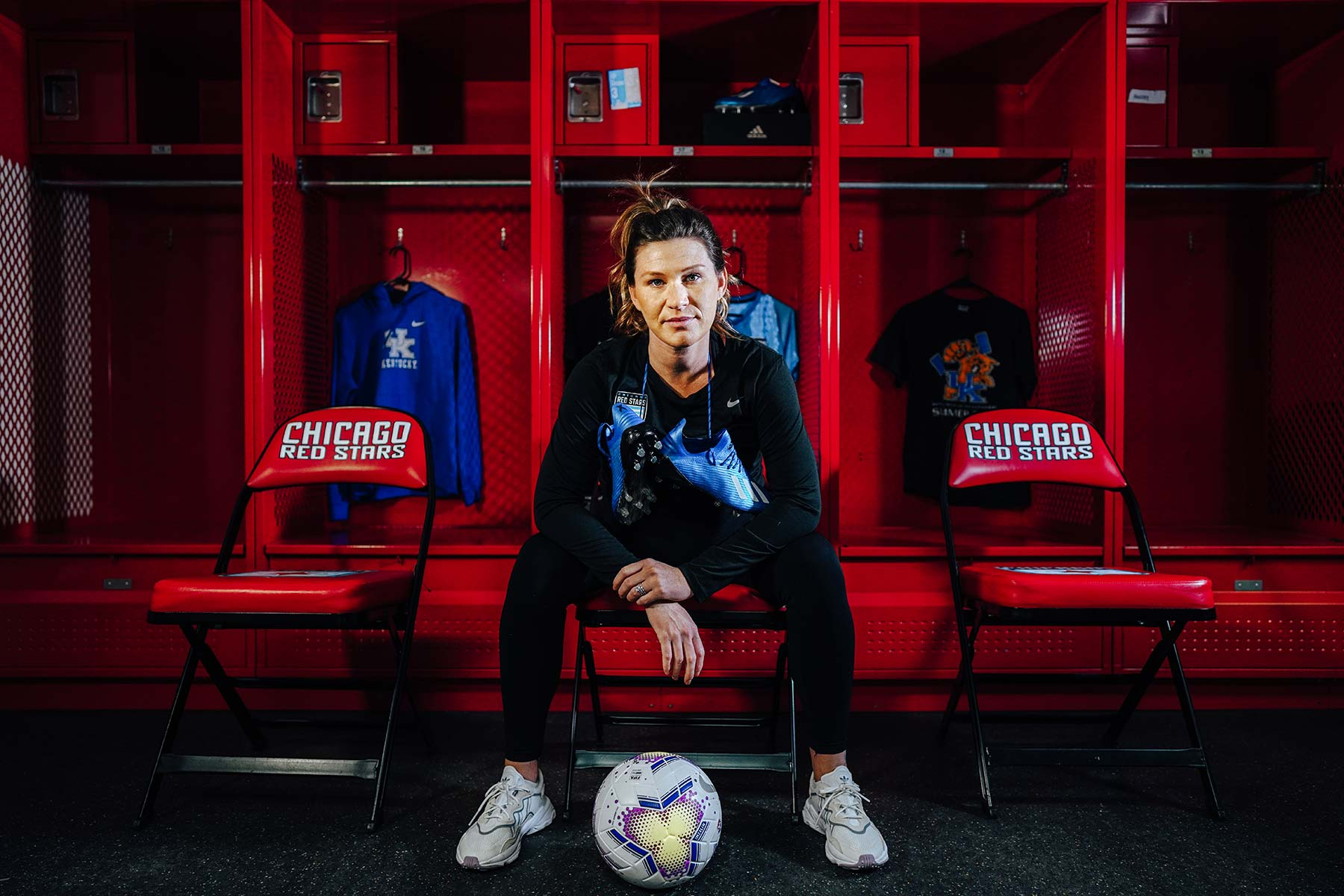 Arin sits in a Chicago Red Stars chair in the locker room with her cleats around her neck and soccer ball at her feet.