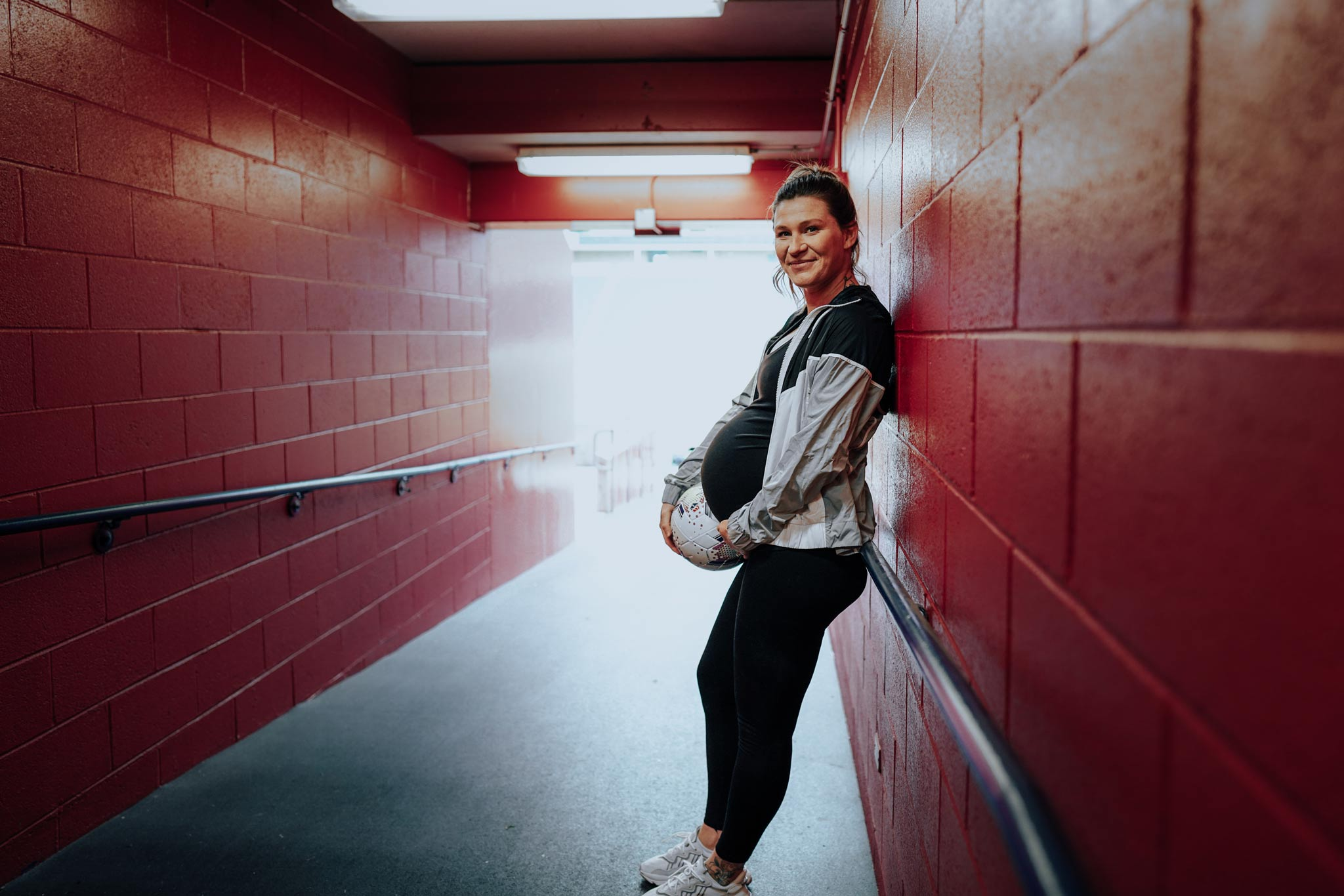 Arin holds a soccer ball next to her baby bump while leaning in the hallway that leads to the soccer field she plays at.