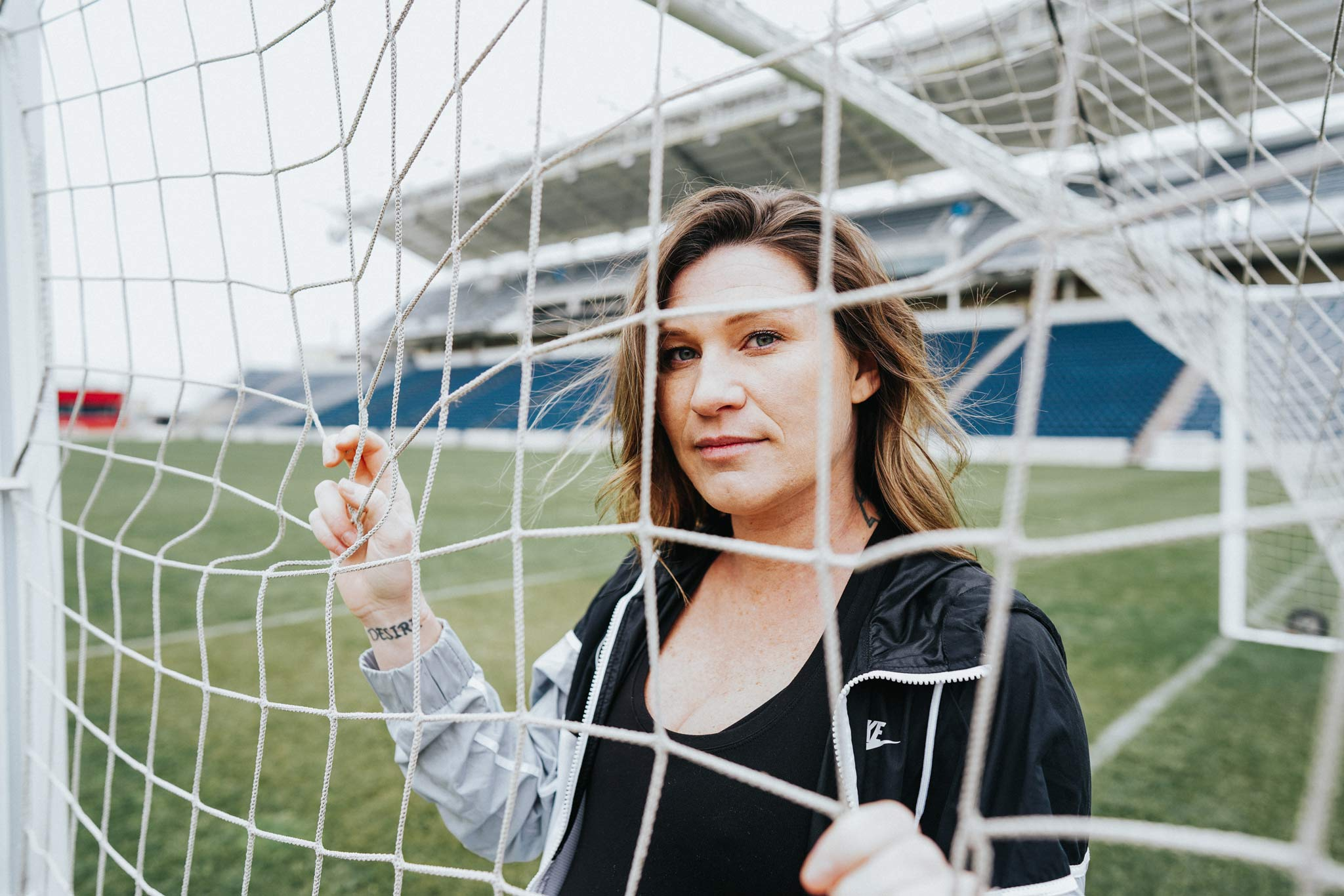 Arin looks through the goal netting while holding onto it.