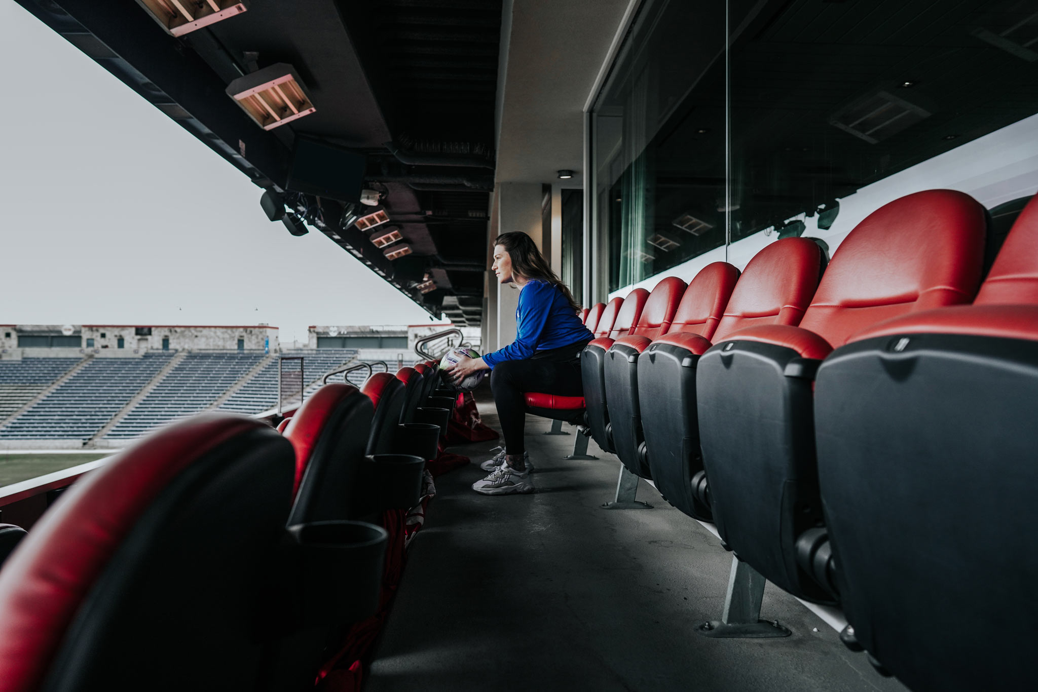 Arin sits in a red seat at the soccer stadium and stares down at the field.