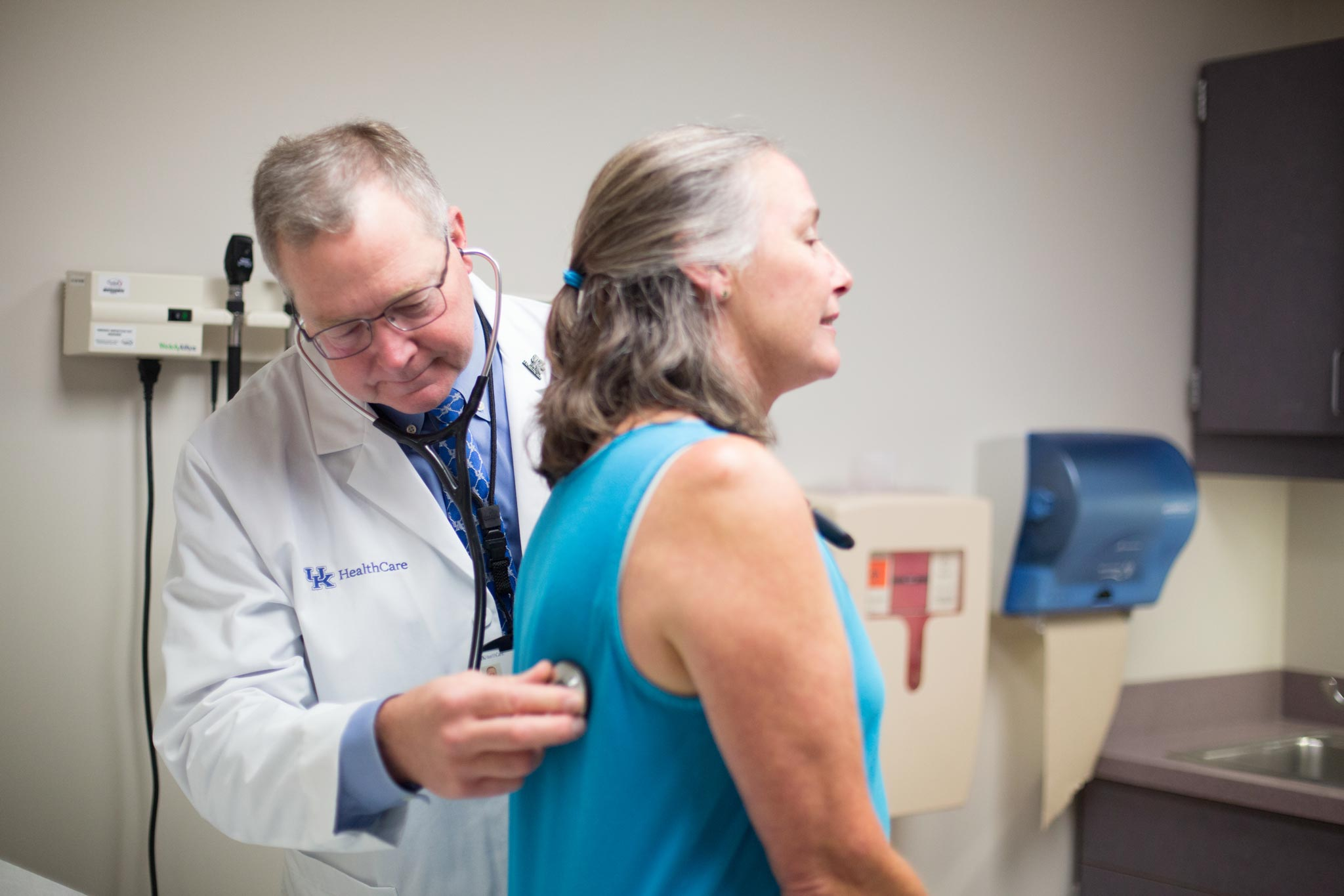 Dr. Mullett listens to a patient's heartbeat with his stethoscope.