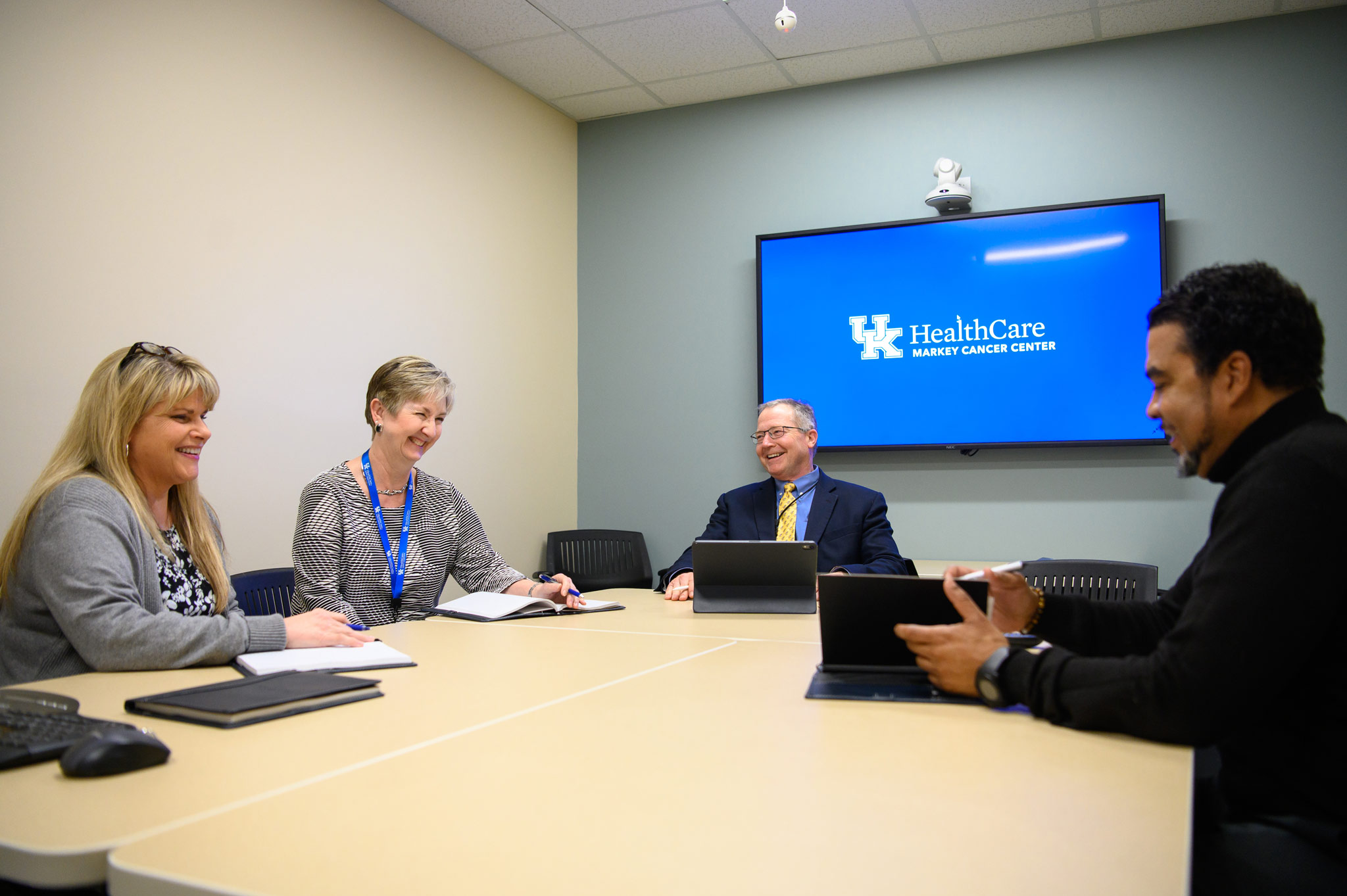 Dr. Mullett and his colleagues smile during a meeting together.