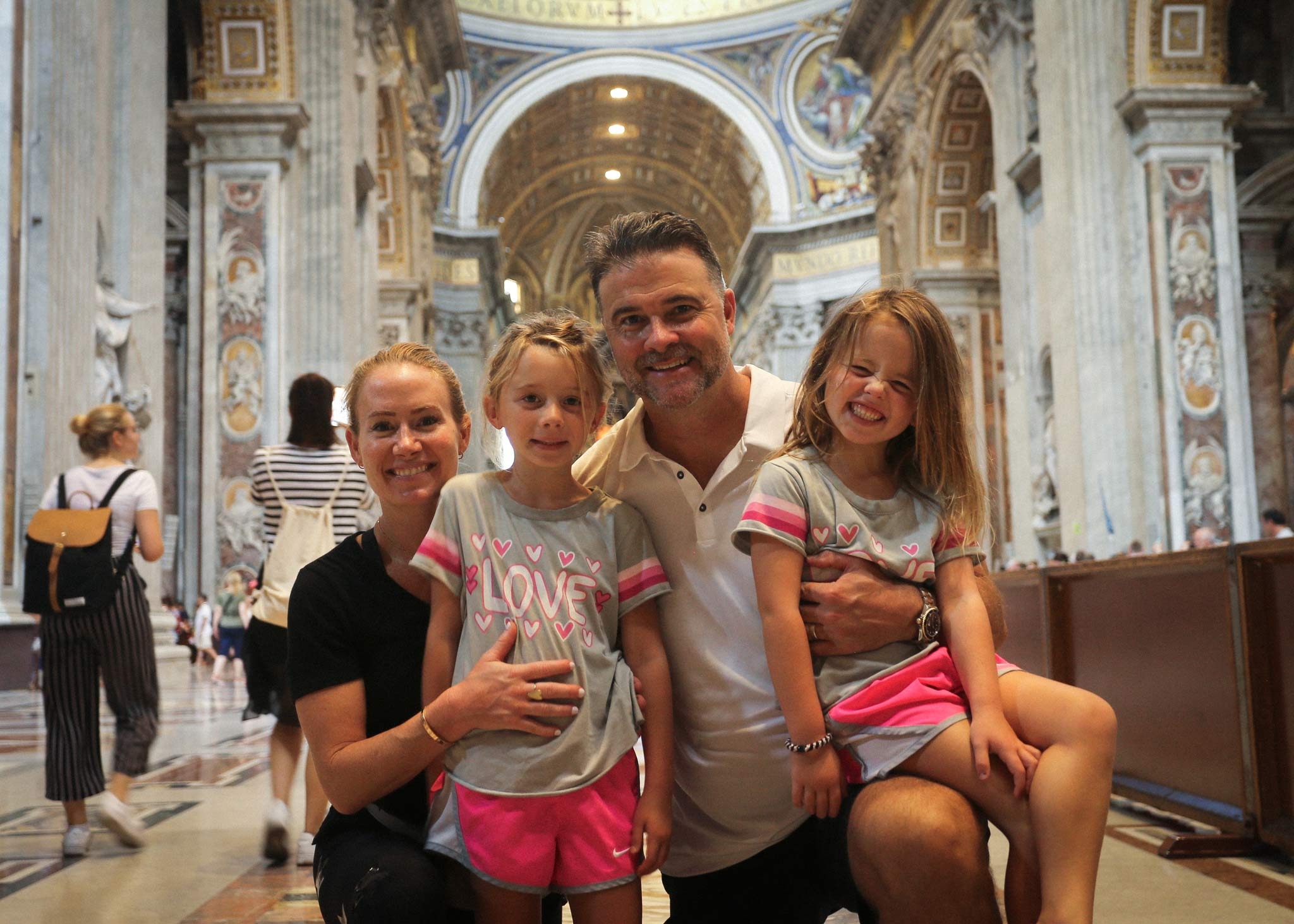 Matthew Mitchell and his wife and two daughters smile for a family photo in an ornate cathedral.
