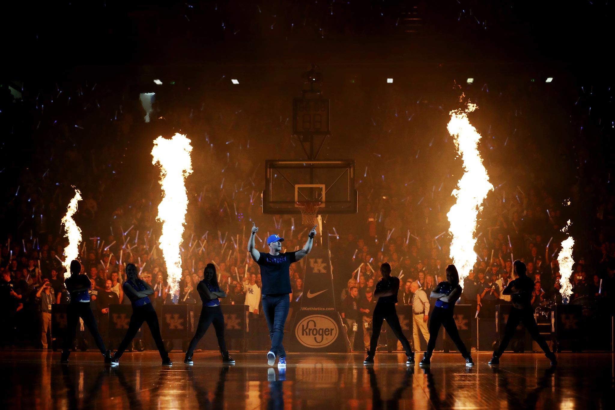 Coach Mitchell dances on the court with the UK dance team dancing behind him and pyrotechnics flaming in the air. The stadium is packed with people.