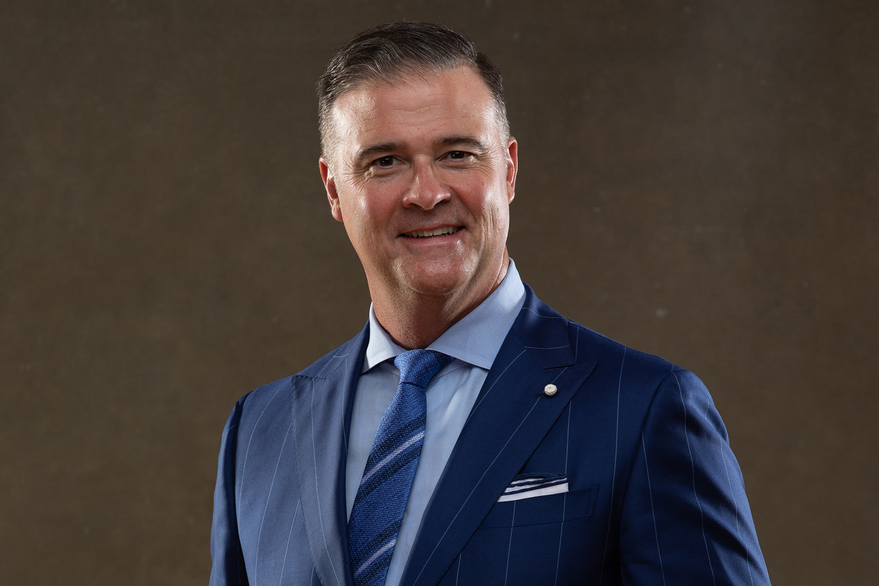 A formal portrait of Coach Mitchell in a blue suit.