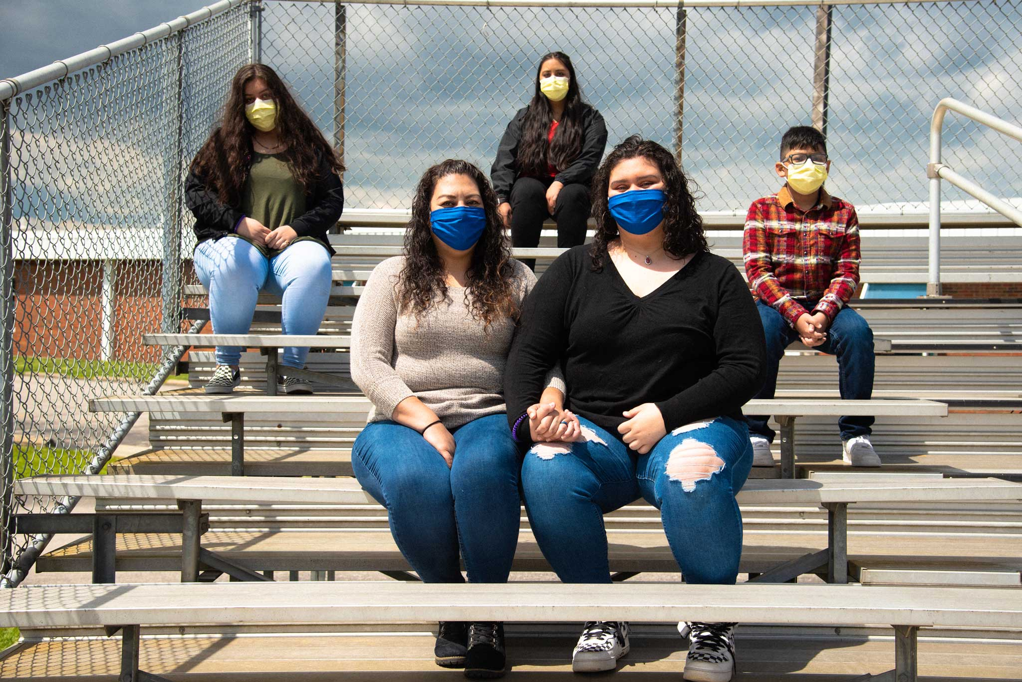 Faith and her mom wear blue face masks and hold hands, while her three siblings wear masks sitting behind them.