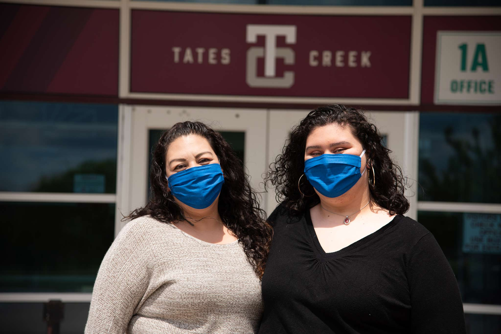 Faith and her mom wear blue face masks and smile in front of the Tates Creek high school front doors.
